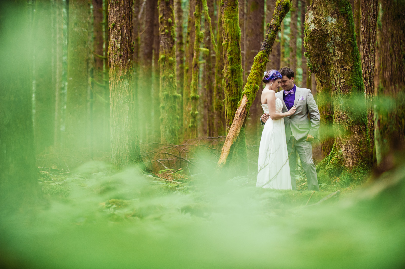 "^ ""Framed by nature.""   This photo of Kaylee and Travis stands out for me this year because I got to shoot it embraces my style of shooting, in one of my most absolute favourite places – the deep, dark woods.  Shooting through the lush foliage on a wet day brought the greenery to life, which seemed to create the perfect contrast against Kaylee's white gown, and the purple in her hair and Travis's suit to make them pop out of the frame."