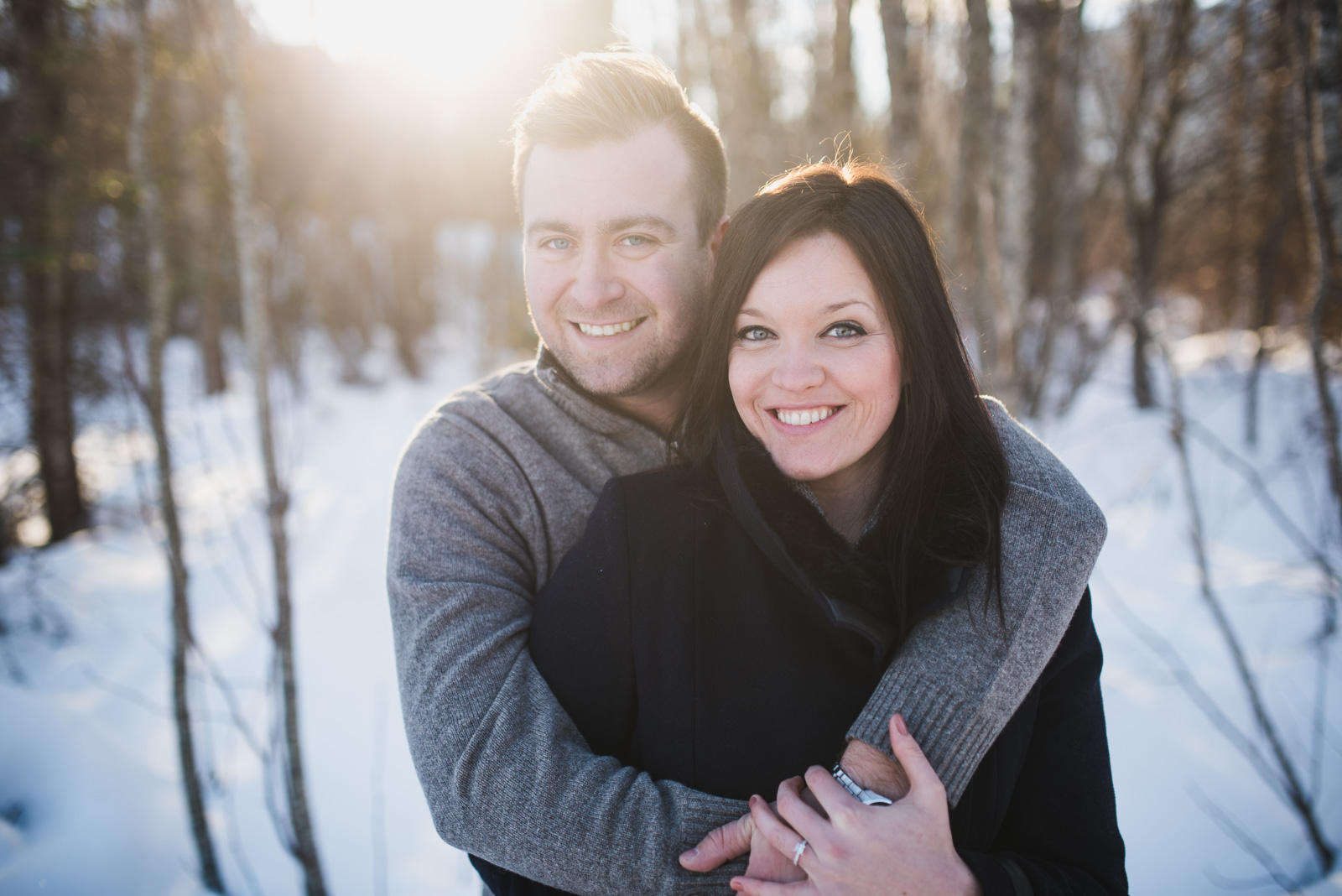 couple standing in the snow with sunflare behind them in whistler - vancouver island wedding photographers