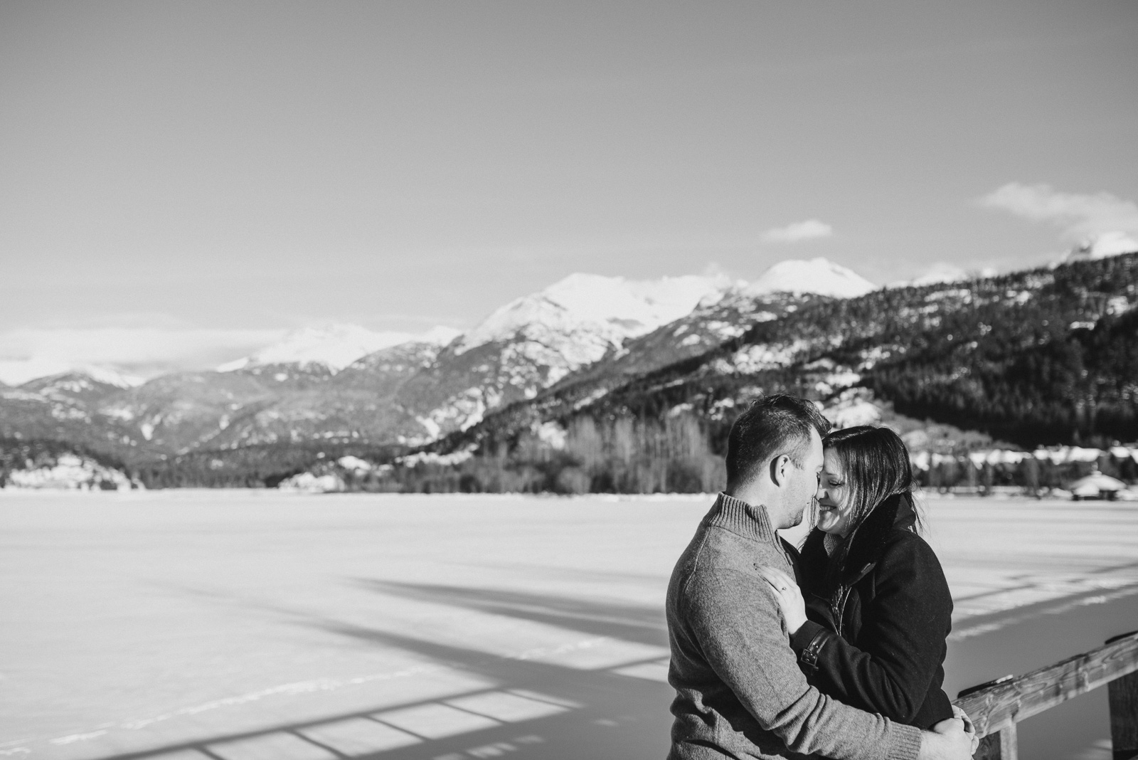 couple standing in front of green lake in whistler on a sunny day - vancouver island wedding photographers