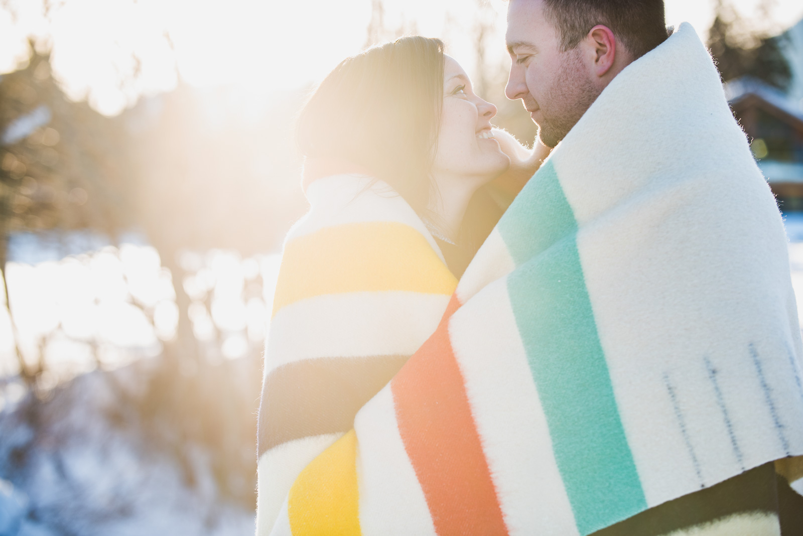 couple standing in the sun wrapped in HBC blanket in the winter - vancouver island wedding photographers