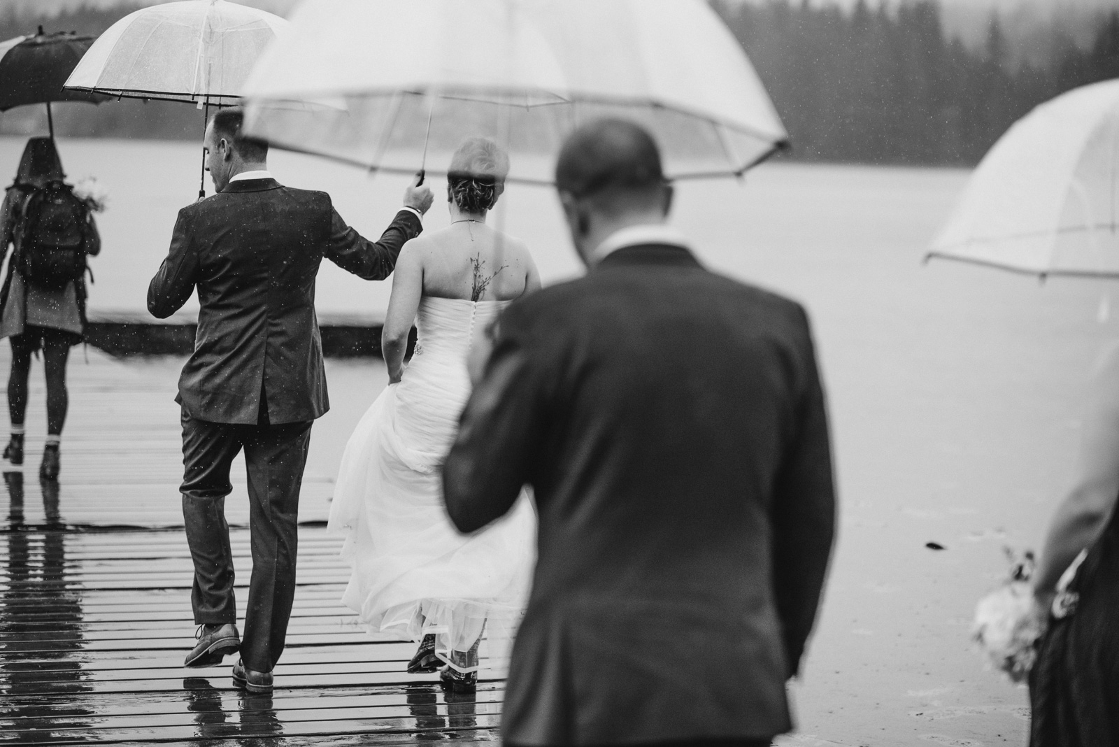 bride and groom walking out onto the dock in the rain at Whonnock Lake Centre in Maple Ridge - Victoria Wedding Photographers