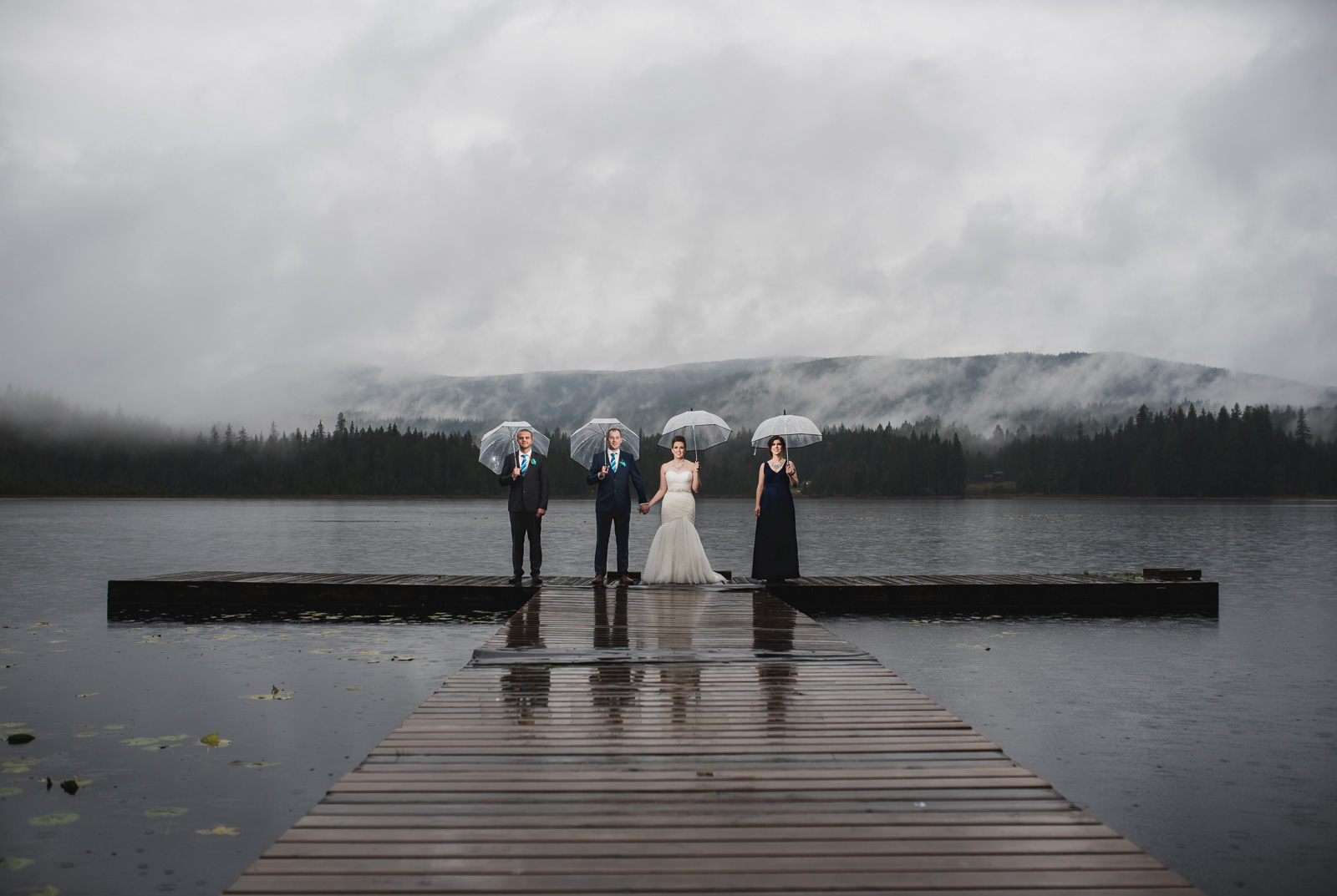 wedding party standing in the rain on the dock at at Whonnock Lake Centre in Maple Ridge - Victoria Wedding Photographers