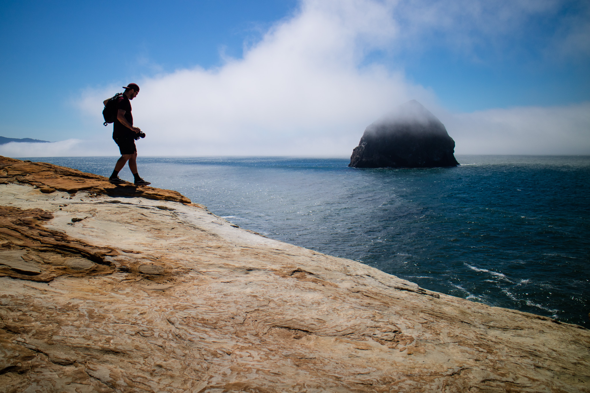 Larryn walking with Haystack Rock in the background.