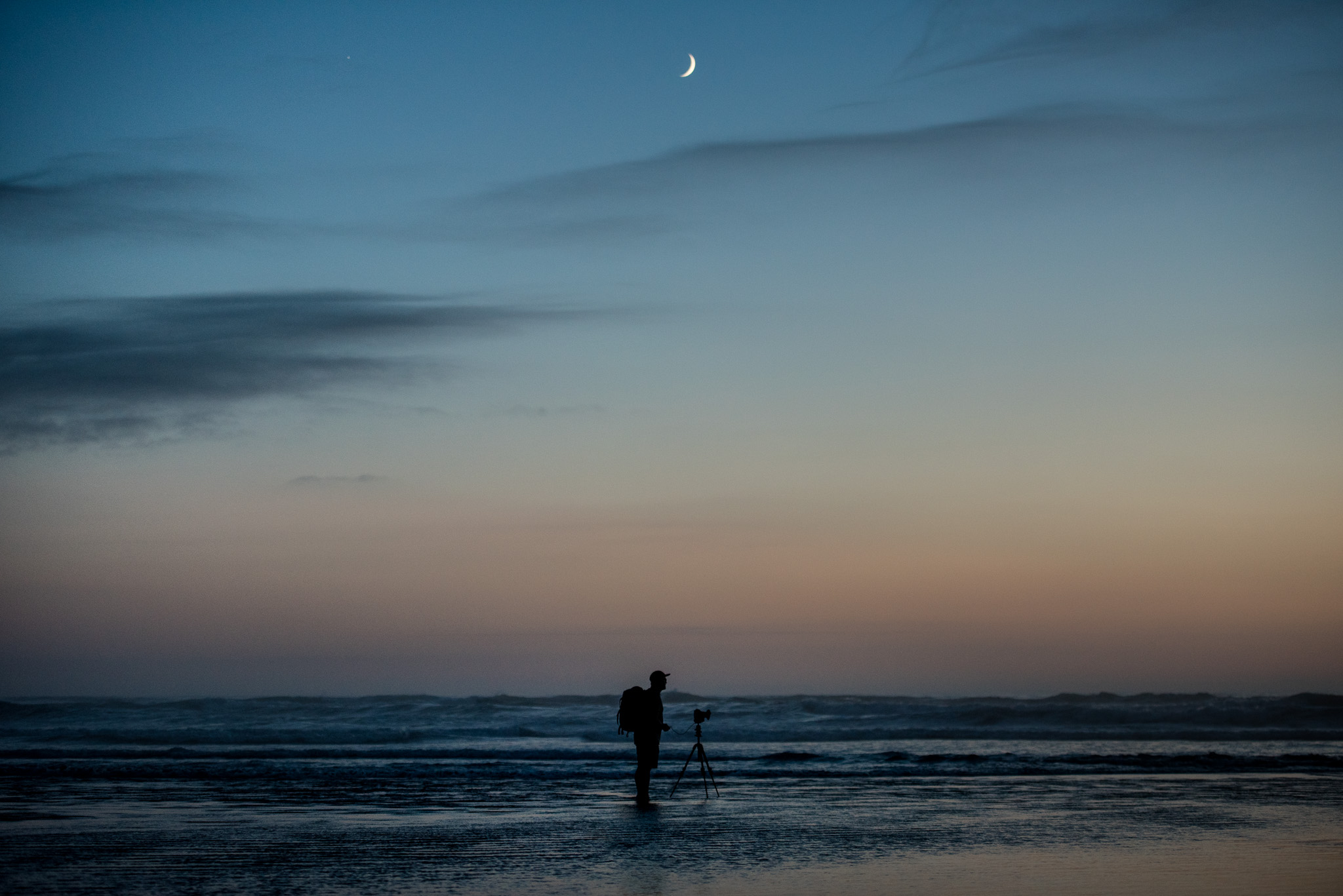 A neat portrait of Larryn standing in the water after sunset with the moon above him, getting his angle at Cannon Beach.