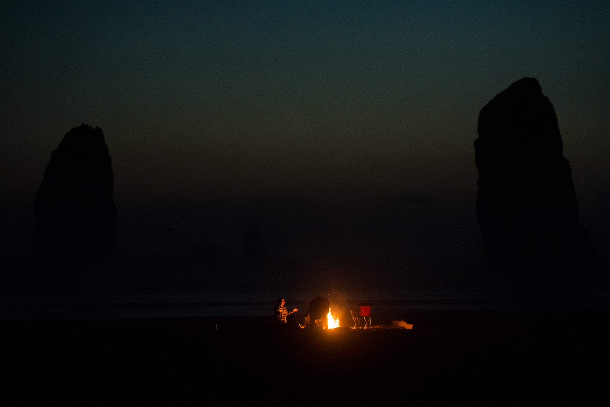 Campfires on the beach with the giant rock formations looming in the background.