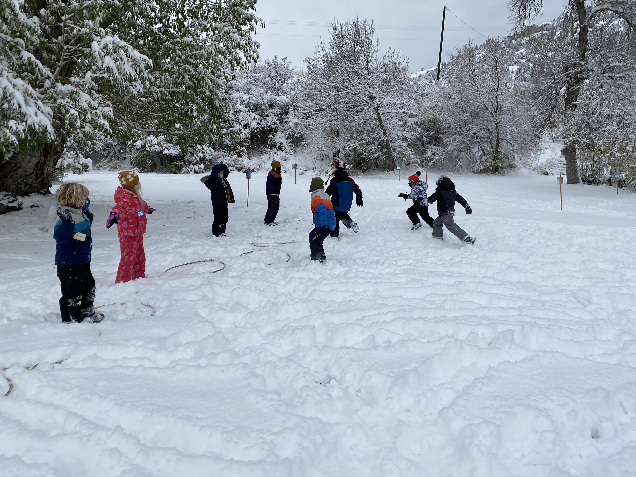 Kids run in snow on the MOSS campus.