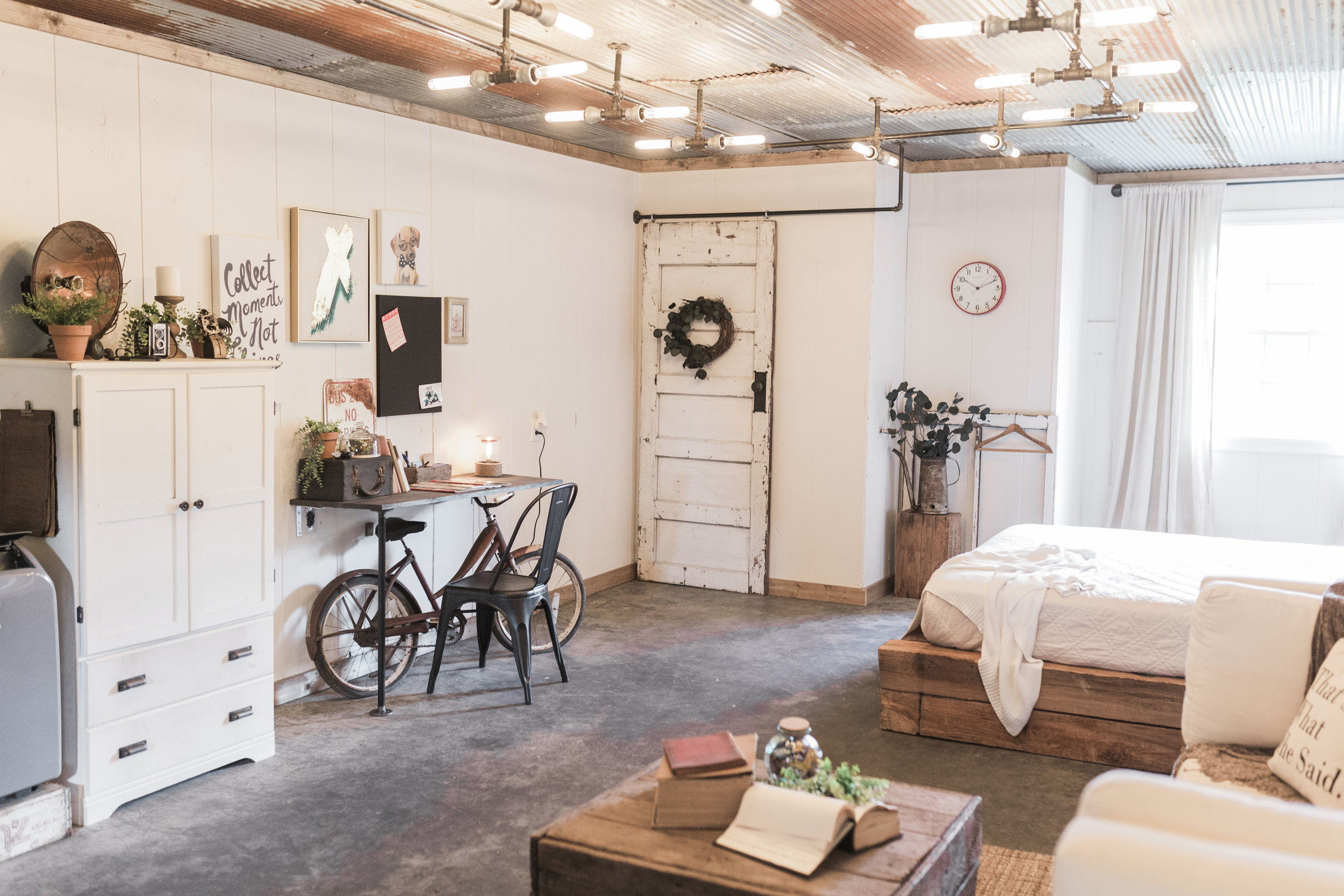 The tin on the ceiling was repurposed from an old shed we had on our property and the platform bed was made from the heavy wood beams from the shed. Much of the decor was found at flea markets and antique stores.