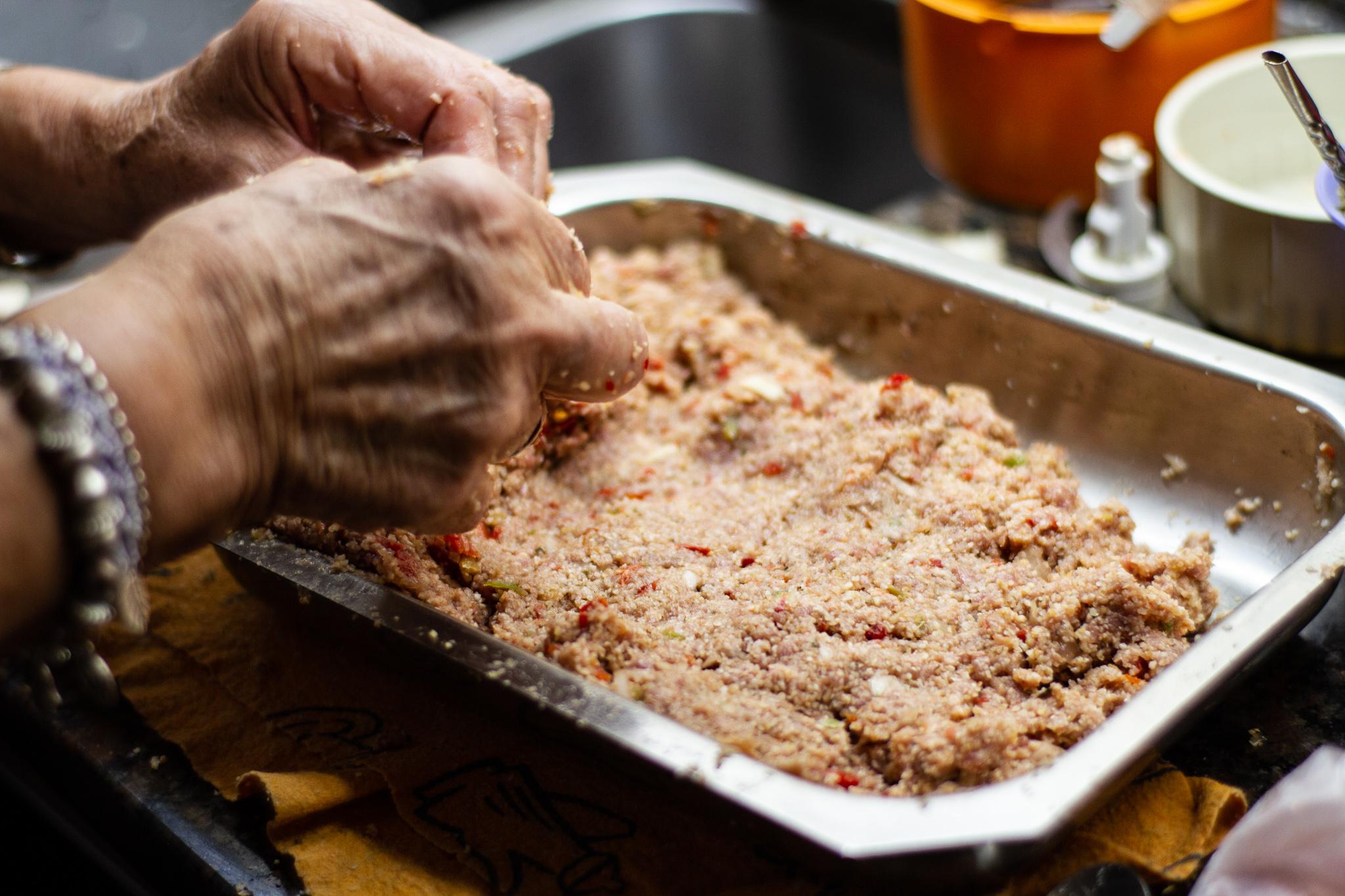 Aida setting kibbi mix into baking dish.