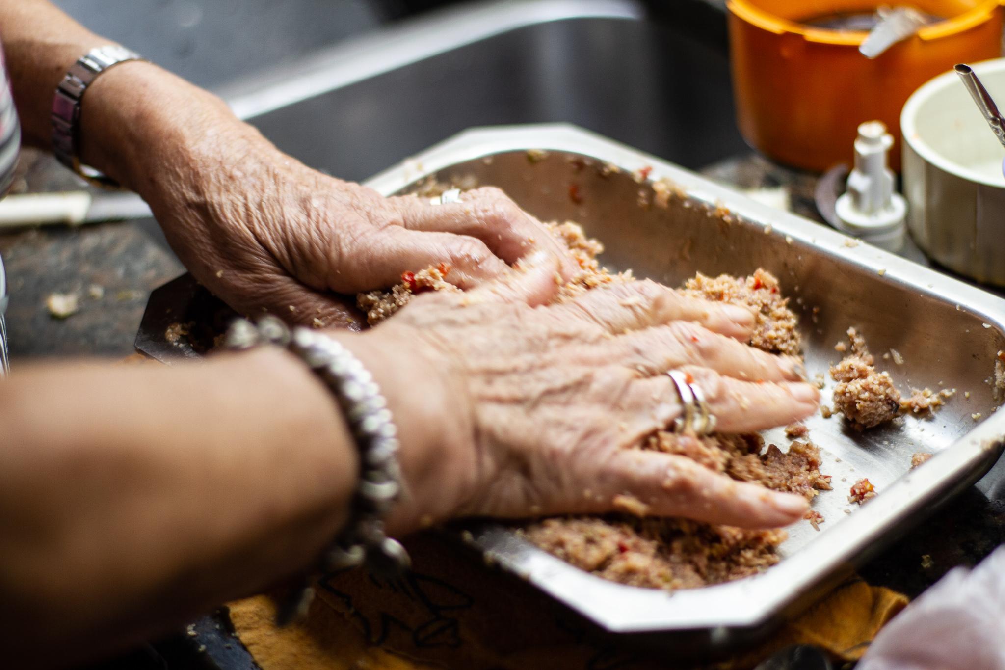 Aida pressing kibbi mixture into baking dish.