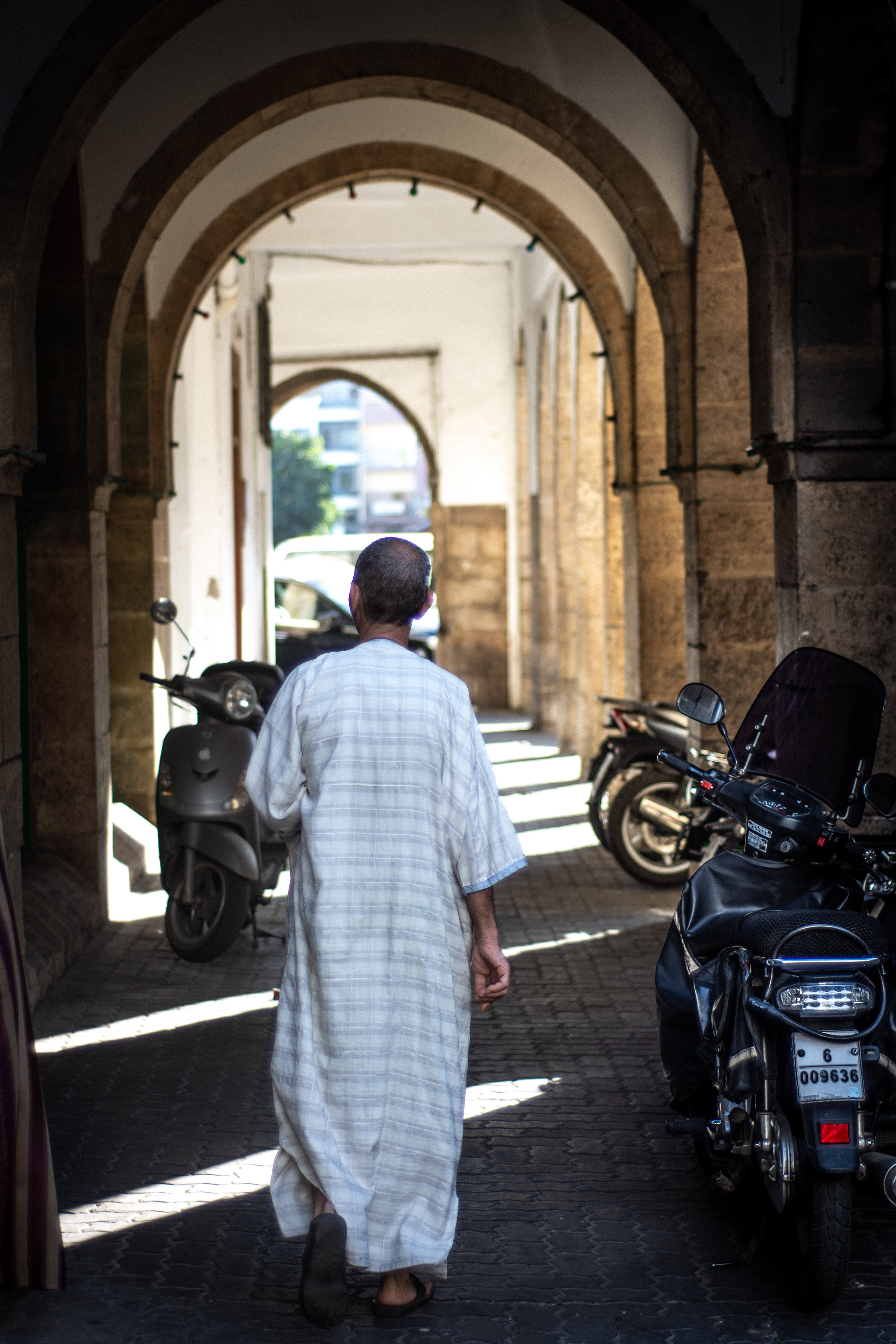 An older man walks along the arched corridors of the medina