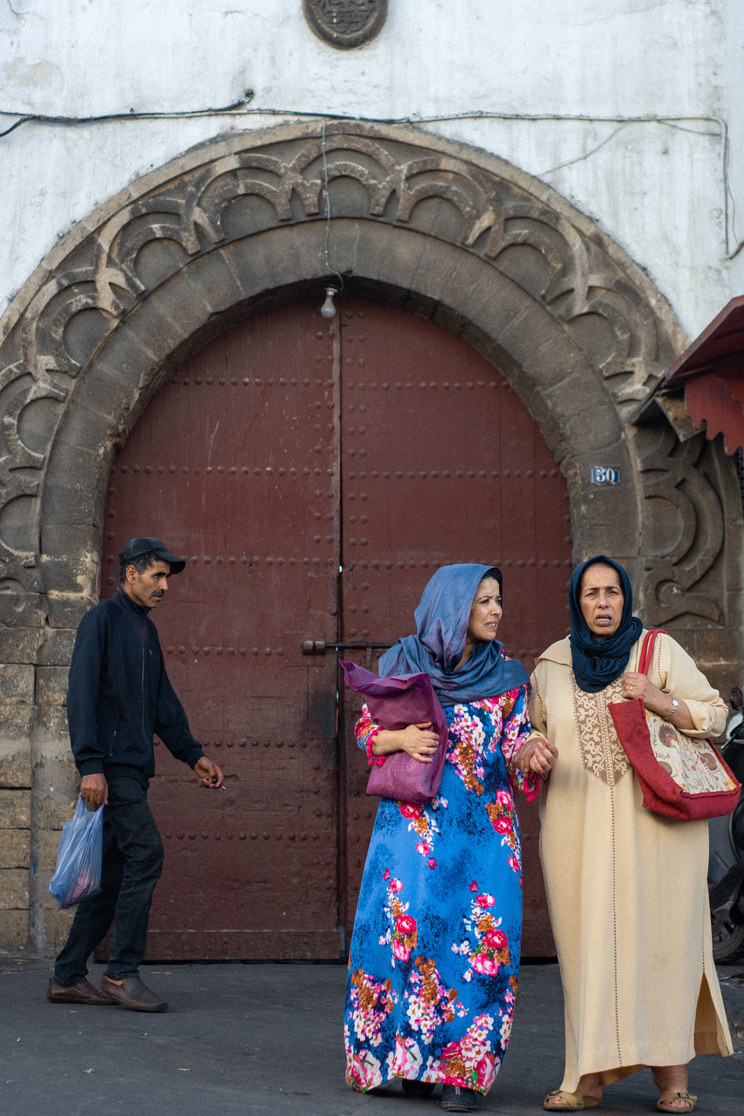 Two women stand outside the wooden doors of the Great Habous Olive Market