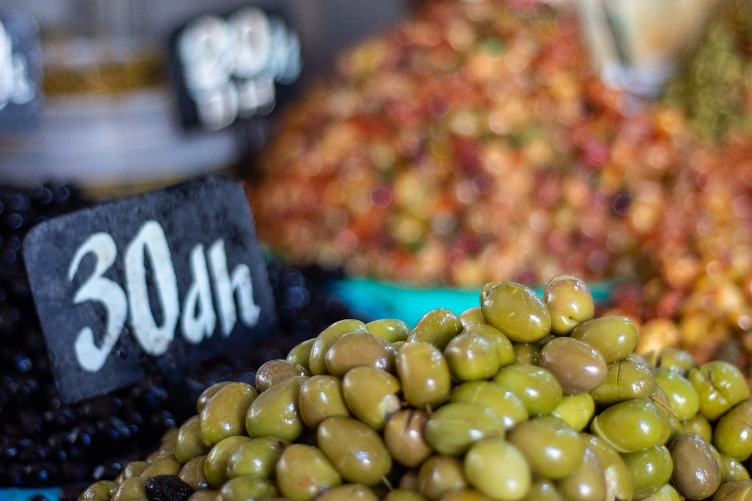 Fragrant mounds of green and cured black olives permeate the market
