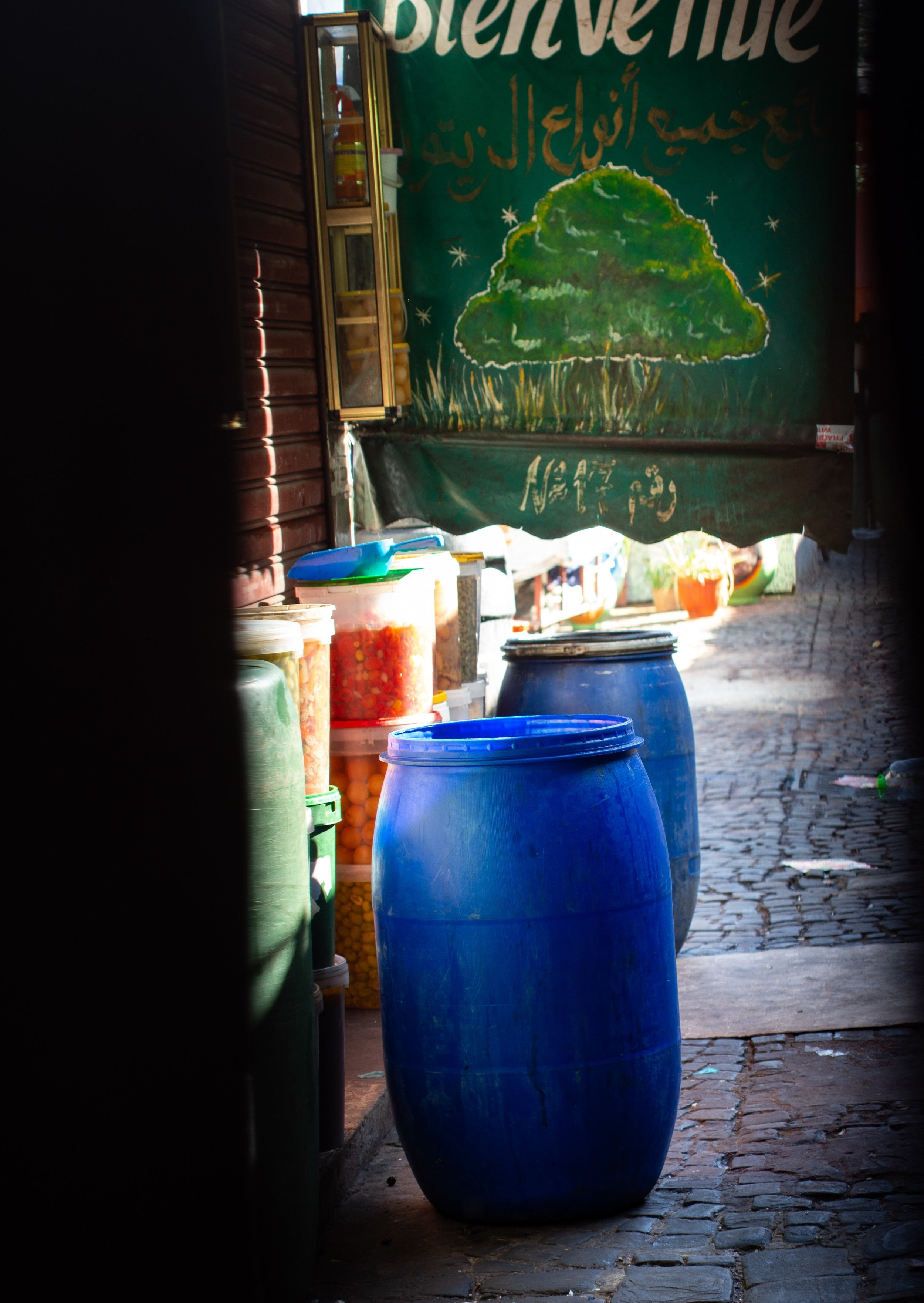 The end of the day; unattended barrels and containers seen through the cracks of the wooden doors of the Great Olive Market, a welcome sign hangs behind them