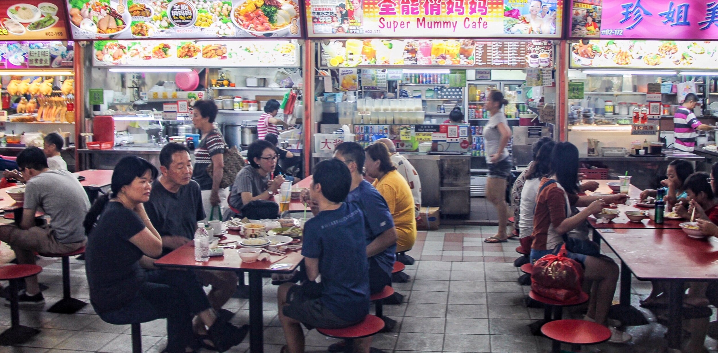 Brightly lit signboards illuminate diners meals at the hawker stalls in Chinatown Food Centre. Each stall displays vibrate photographs of their specialty dish.
