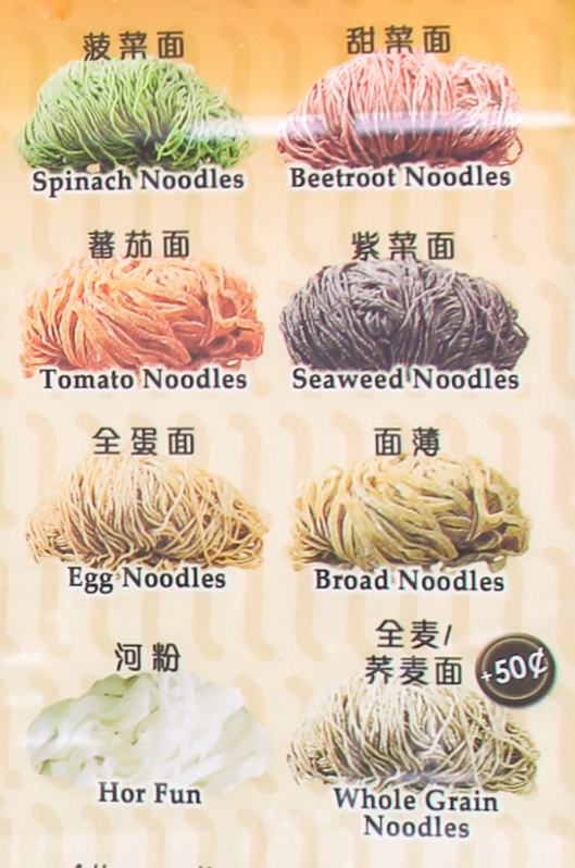 """Outside the Cho Kee Noodle stall, a sign advertising their homemade vegetable noodle selections reads,""""All noodles sold are solely made by Cho Kee with high-quality flour, fresh eggs and are low in sodium & additives. All Veggies Noodles contain real vegetables."""""""