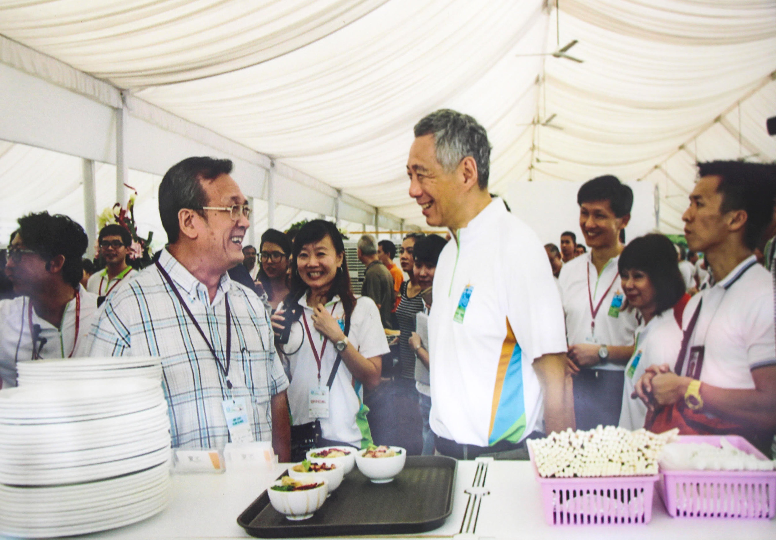 Cho Kum Kong serving Cho Noodles to Singapore's current Prime Minister, Lee Hsien Loong, at a food fair.