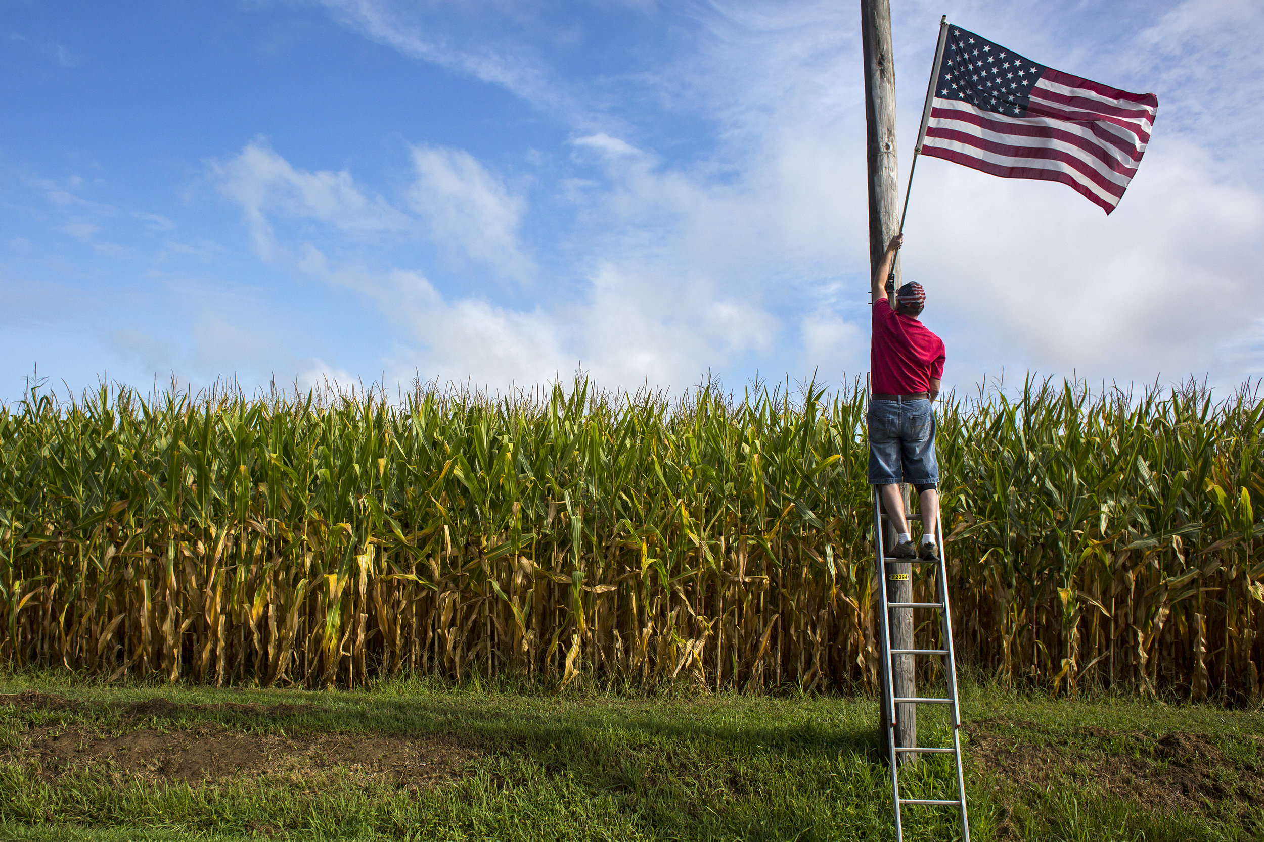 """For 30 years, Bob Meyer has placed American flags along roadways in his hometown of St. Henry. """"What started out as just decorations went much, much deeper. It's the symbol of freedom,"""" Meyer said Sept. 2 after completing a round of flag placement. """"And that ties in big time with all these veterans here in this town."""" He said his mother, Nip Meyer, was on the decorating committee when the community celebrated its 125th anniversary in 1987 and asked him to put up the flags initially. Three decades later, Meyer is still placing the flags out for Labor Day, Memorial Day, Fourth of July, Veterans Day, September 11 and the community's annual festival. """"When I started I thought, 'Well I'll do them as long as my mom wants me to,"""" he said. """"And then bless her heart, she's still here today for this 30th anniversary."""" — Sept. 2, 2017, St. Henry, Indiana."""