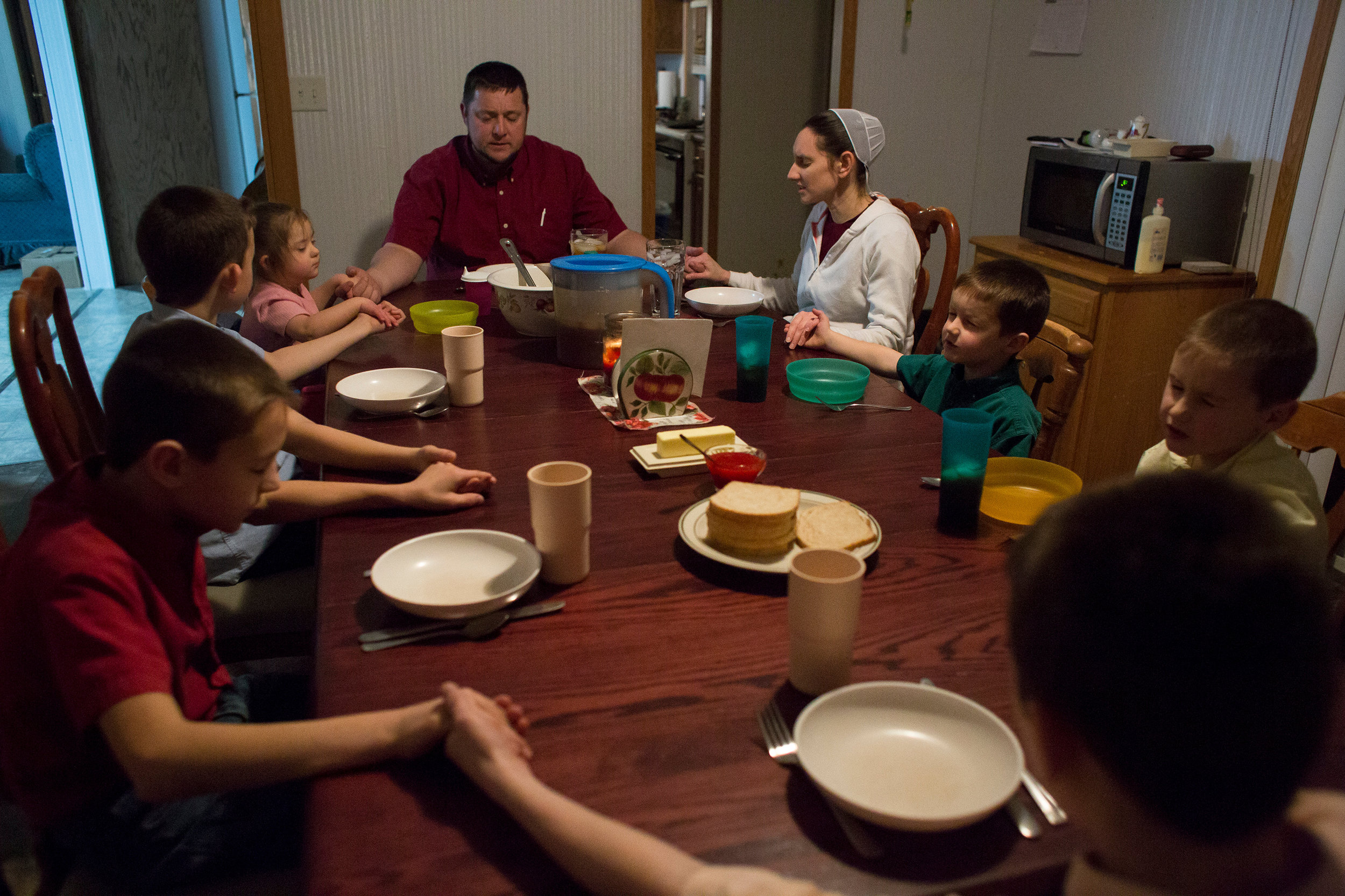 "Stanley Knepp along with his wife, Shannon, and their children — Bryant, 12, Cody, 11, Darius, 10, Tyler, 8, Zachary, 5, and Andrea, 3 — sang ""Be Present at Our Table"" as a song of grace before eating dinner in their Loogootee home Dec. 30. Stanley, who described his family's beliefs as on the more conservative side of the Mennonite faith, said the family will sometimes sing a ""grace song"" before a meal, as opposed to a nonmusical prayer. He said his family will always dismiss from the table with a song."