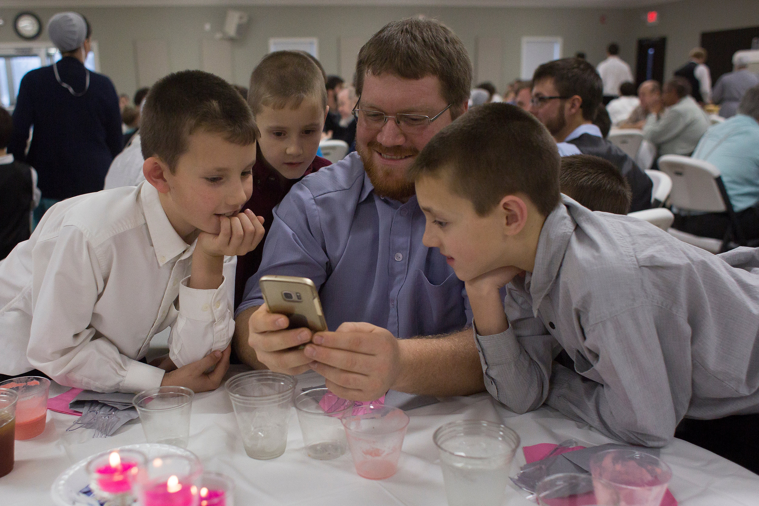 Jonathan Beachy of Flat Rock, Illinois, showed hunting videos to the Knepp children — Darius, Tyler, Zachary, and Cody — on his phone during a wedding reception Dec. 22 at Berea Mennonite Church in Cannelburg. The Knepps do not have a television or radio in the home and computer access is limited to roughly 20 minutes per child each week. Although the Knepp family does make use of email and the internet, Stanley said social media platforms such as Facebook, Twitter and Instagram are prohibited by their church.