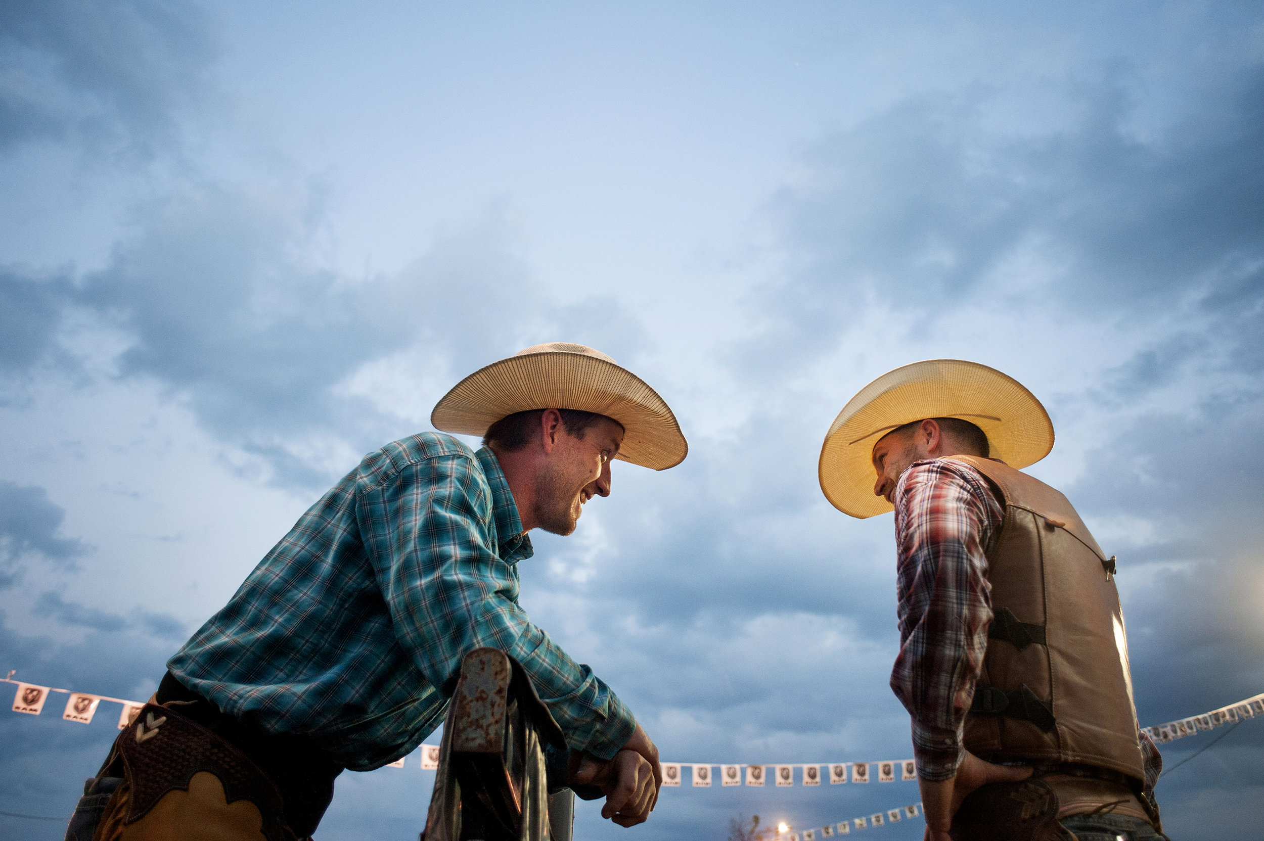"Kirk Nelson, of Branson, Mo., and Keith Brauer, of Belleville, Ill., speak before the start of their competitions. ""For me, it's just keeping the American West alive and letting people know that cowboys are still out there,"" Brauer said. ""It's a way of life. Most of all these guys will do it for nothing. Will do it for free because they just love it."""