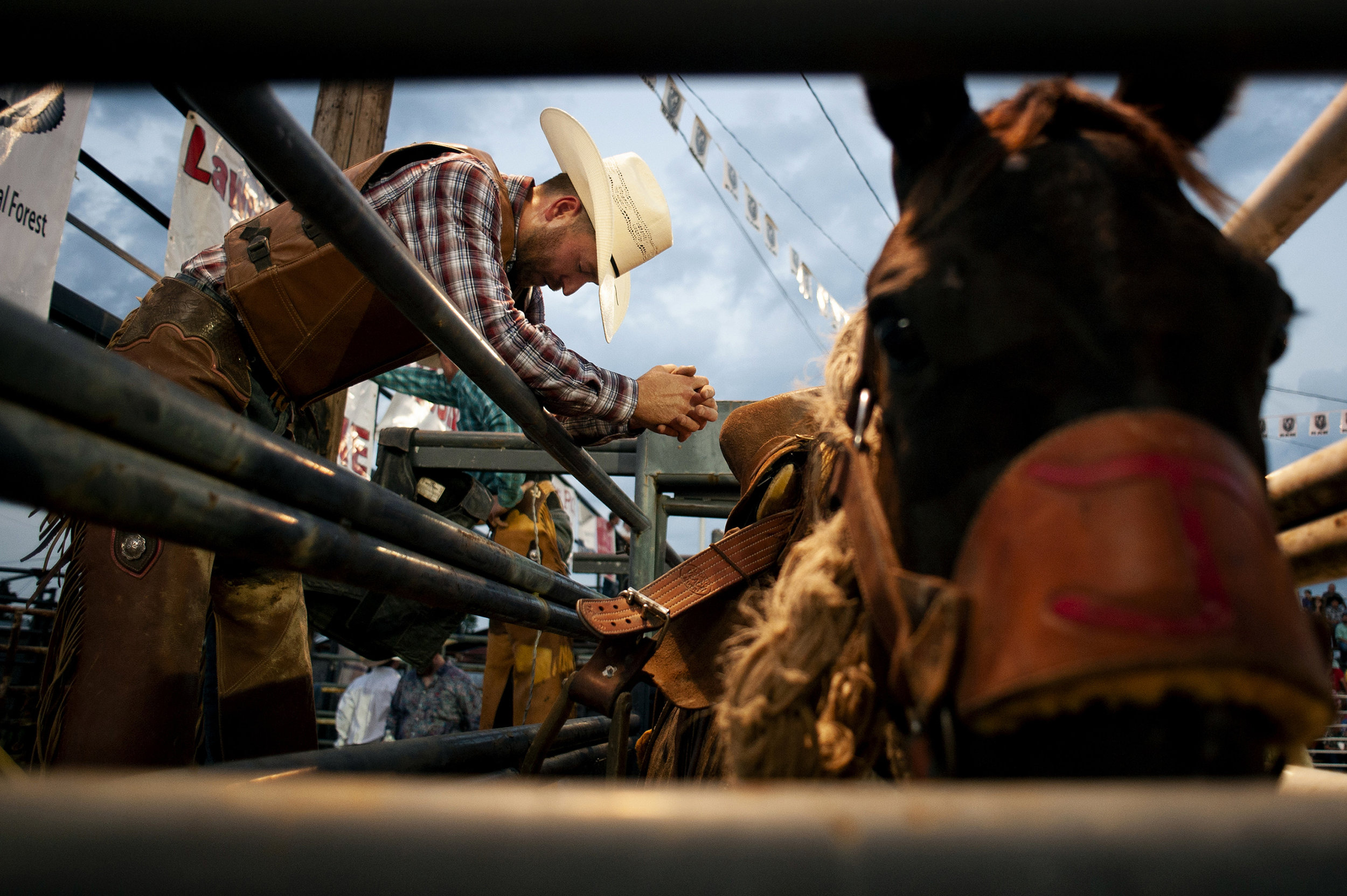 "Brauer takes a moment to collect himself before his saddle bronc competition. Brauer, who shoes horses for a living and makes part of his income through rodeo, prays at competition and said religion is everything to him. ""I pray to keep my family safe, keep me safe, keep the bucking stock safe,"" he said. ""Everybody that's here."""