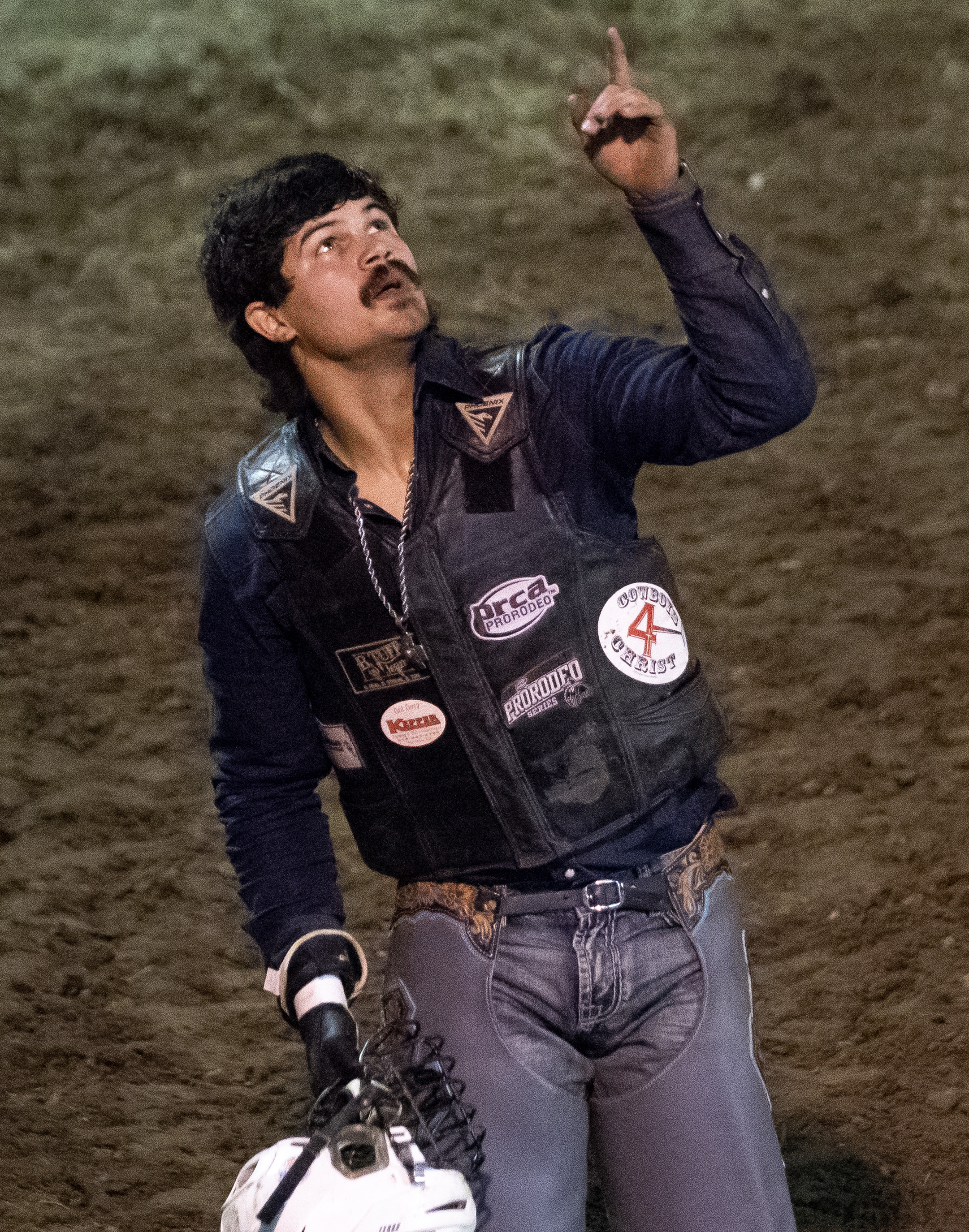 "Mincey points toward the sky while celebrating successfully riding his bull for a full eight-second ride. Mincey, who turned 24 the day following rodeo, won the bull riding portion of the event. ""Cowboys is a dying breed,"" Mincey said while speaking about rodeo. ""So each day that we get to do it is a blessing."""