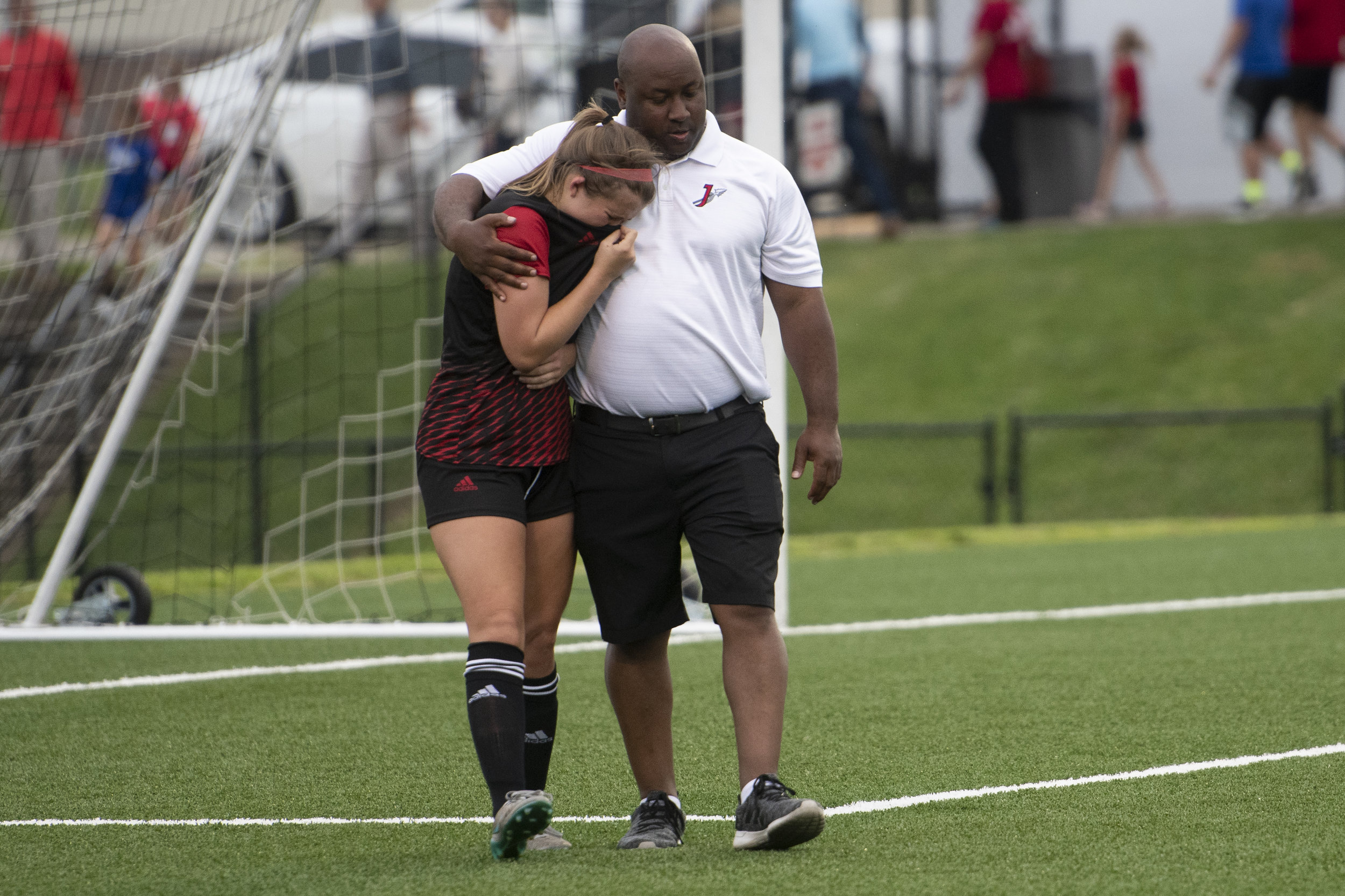Following an opposing overtime goal ending the Jackson Indians' season, Jackson's Taylor Nelson (7) is consoled by head coach Justin McMullen shortly after the Indians' 2-1 overtime loss to Lindbergh High School in the Class 4 sectionals Tuesday, May 21, 2019, in Jackson. Jacob Wiegand | Southeast Missourian
