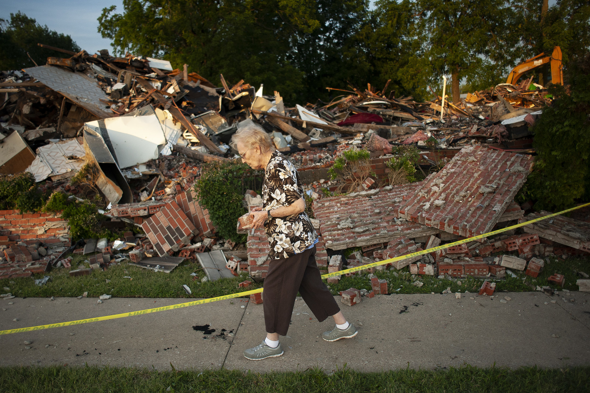 """Arleen Tipsword, who at age 90 believes herself to be the oldest member of Cornerstone Wesleyan Church, takes a brick as a souvenir from the remains of the church June 22 at 210 E. Outer Road in Scott City, Missouri. """"It's heartbreaking,"""" Tipsword said of the building that was destroyed in a fire during Friday afternoon's storm. """"I met my husband here in this church."""" She believes it was 1978 when she first attended the church where she would marry her husband in 1985. """"I mean this is most wonderful church family that we can depend on,"""" she said. — June 22, 2019, Scott City, Missouri."""