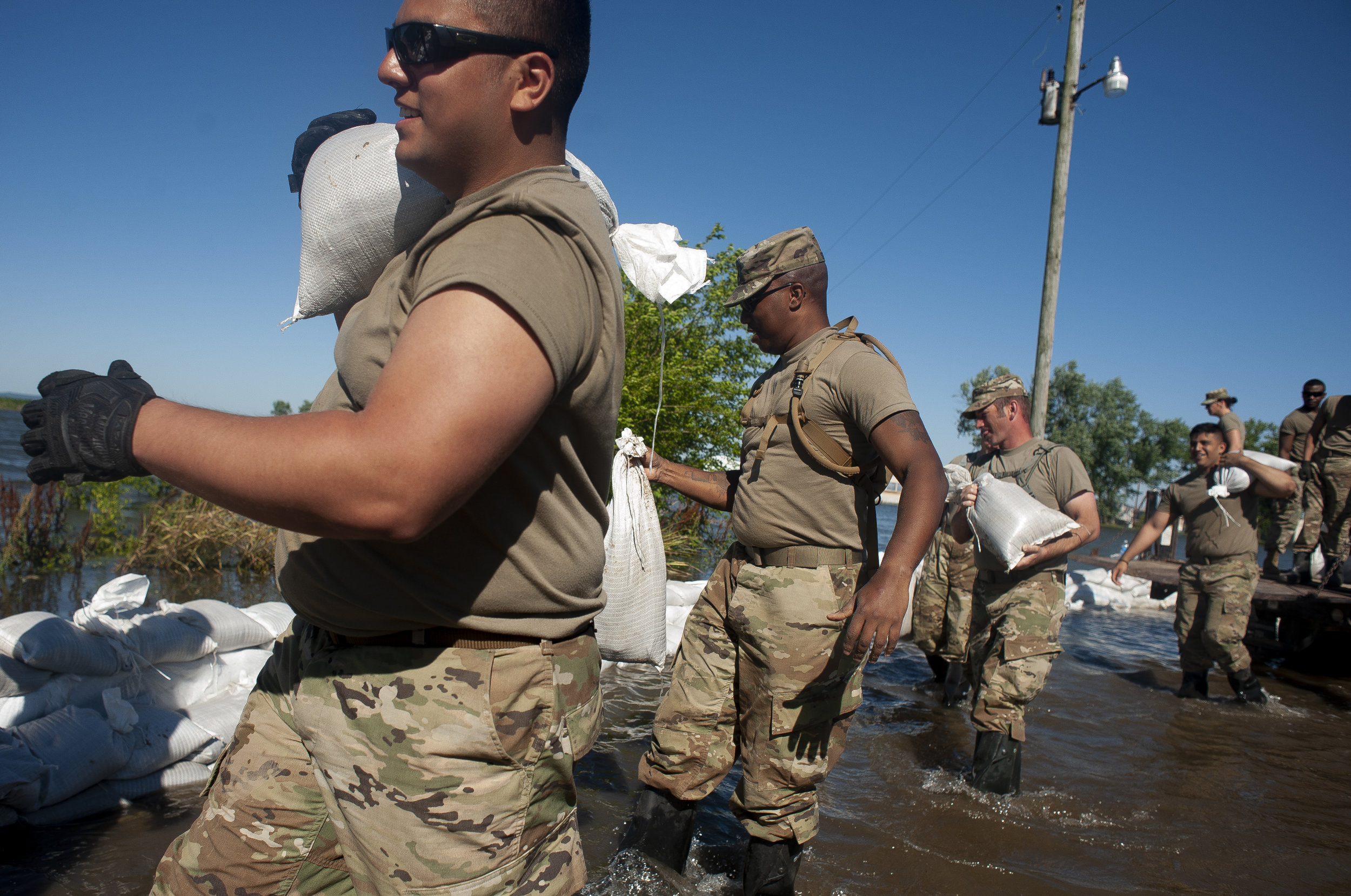 Illinois National Guard member Arturo Martinez, front, and other Guard members help build up sandbag barriers to hold back floodwaters Monday, June 10, 2019, along Brookwood Drive in East Cape Girardeau, Illinois. Jacob Wiegand | Southeast Missourian