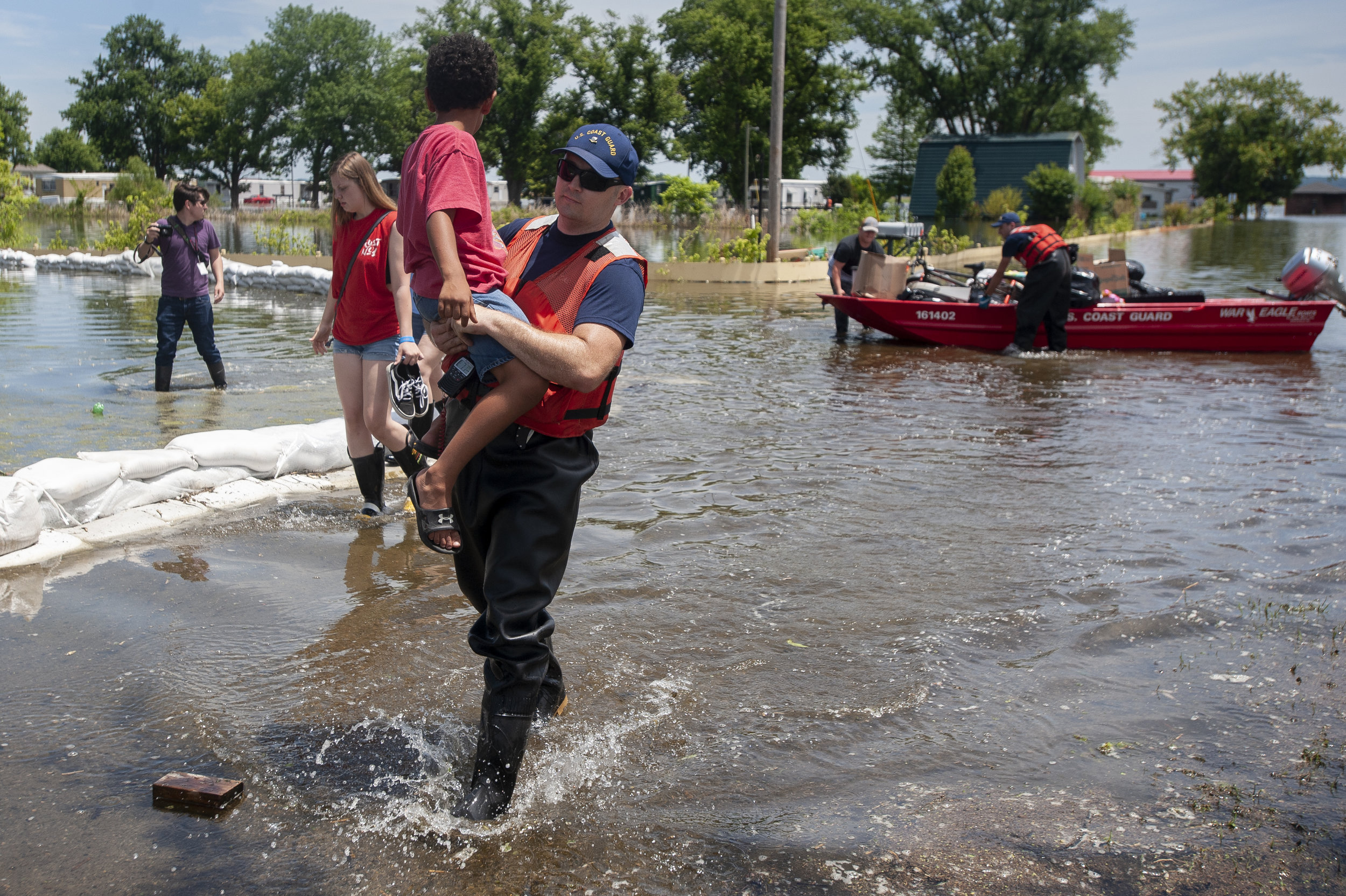 "Rich Lehman, of the U.S. Coast Guard, carries Izayah Gilbert, 7, a resident of trailer park on the northeast side of East Cape Girardeau, Illinois, next to Aubrey Walters, 15, also a trailer park resident, as the trailer park evacuates Tuesday, June 11, 2019, in East Cape Girardeau. ""We have nowhere to really turn,"" trailer park resident Brandi Walters said. ""I have a couple friends that is willing to open their home to us."" Walters, who lives with her daughter and boyfriend, said they are staying with friends Tuesday night. In response to area flooding, an American Red Cross shelter opened Tuesday at Spark Ministries Church at 40842 Illinois Route 3 in McClure, Illinois, according to a news release from American Red Cross of Missouri and Arkansas. Those coming to the shelter should bring: a few days worth of clothing, bedding including pillows and blankets, toiletries, essential medication and items for children. Jacob Wiegand 