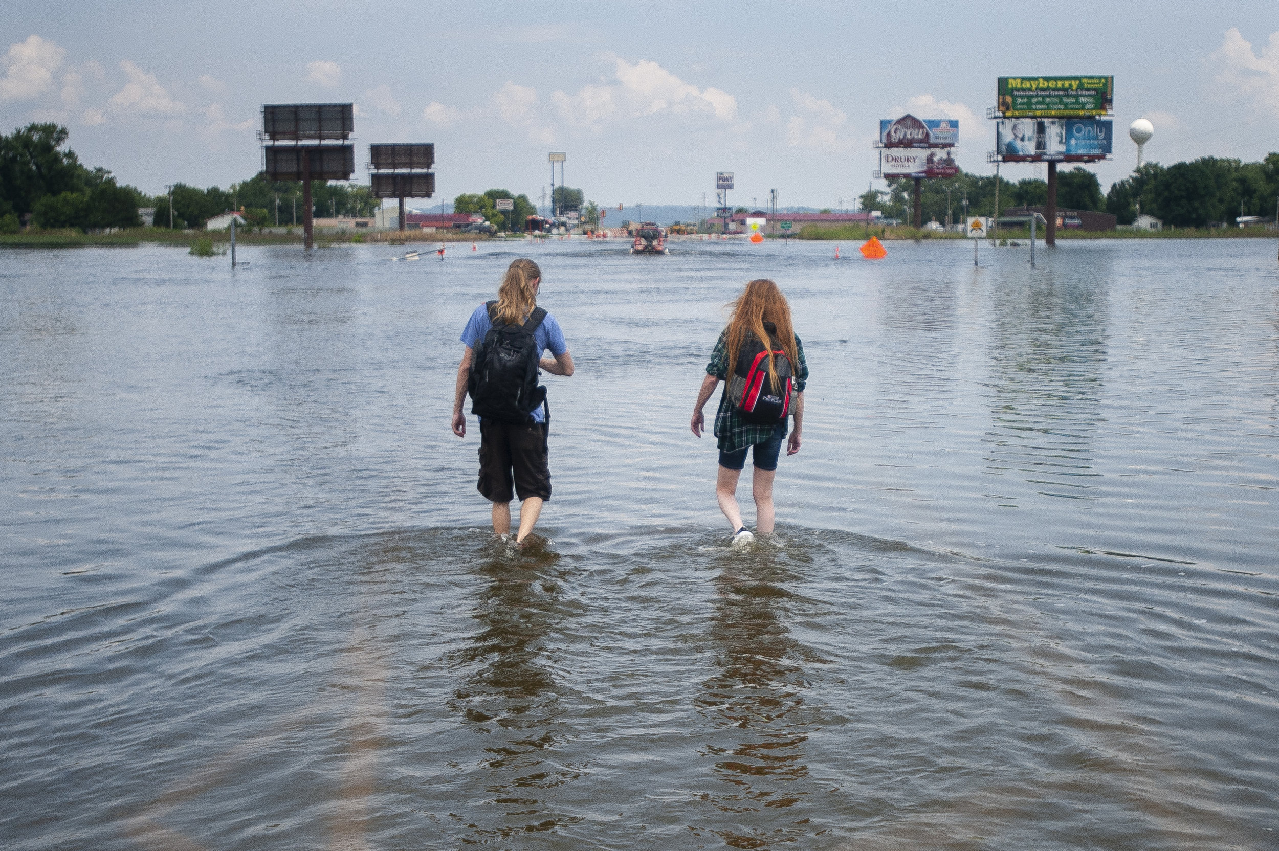 "Cindy Laymon, right, and her son Jesse Laymon-Sheffer, both of East Cape Girardeau, Illinois, walk back to the community from their parked vehicle Tuesday, July 9, 2019, through a flooded portion of Illinois Route 146 between the Bill Emerson Memorial Bridge and the edge of East Cape Girardeau. The mother and son have been parking a vehicle at the edge of floodwaters to travel to work in Cape Girardeau. ""We have come to work every day so it's at least two trips [through the water],"" Cindy said of their routine for most days. Jacob Wiegand 
