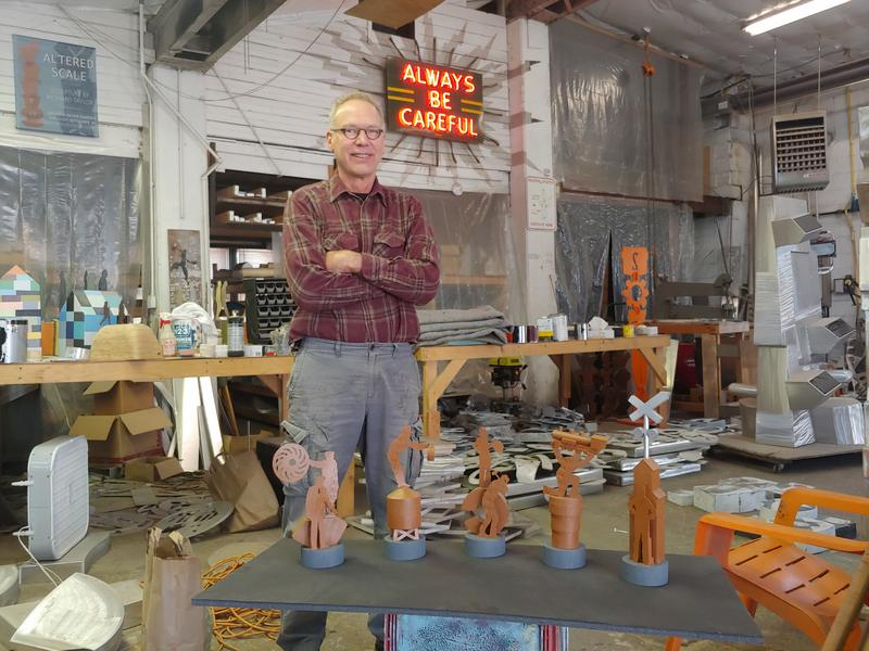 "Milwaukee sculptor Richard Taylor stands in his Riverwest studio. Before him is a maquette, or scale model, of the ""People of the Road"" monument.   CREDIT CHUCK QUIRMBACH"