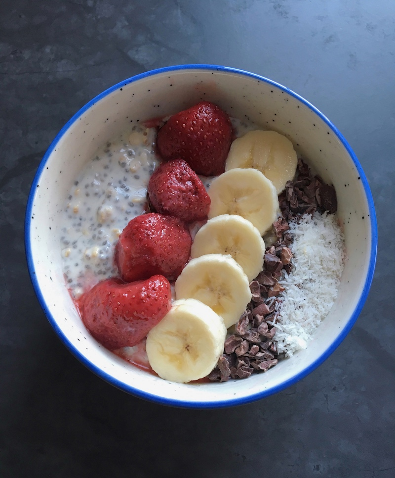 Overnight oats topped with strawberries, banana slices, cacao nibs, and coconut flakes to fuel a busy day