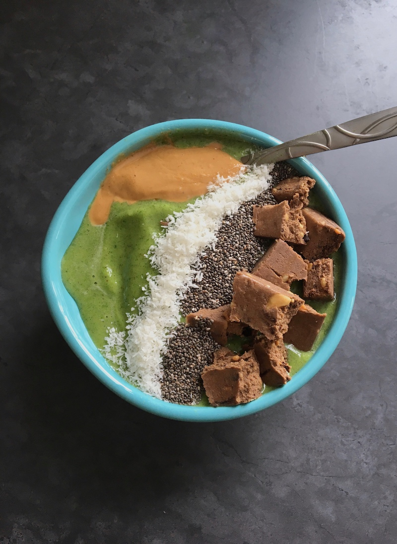 Green smoothie bowls topped with cashew butter, coconut flakes, chia seeds, and a  Perfect Bar