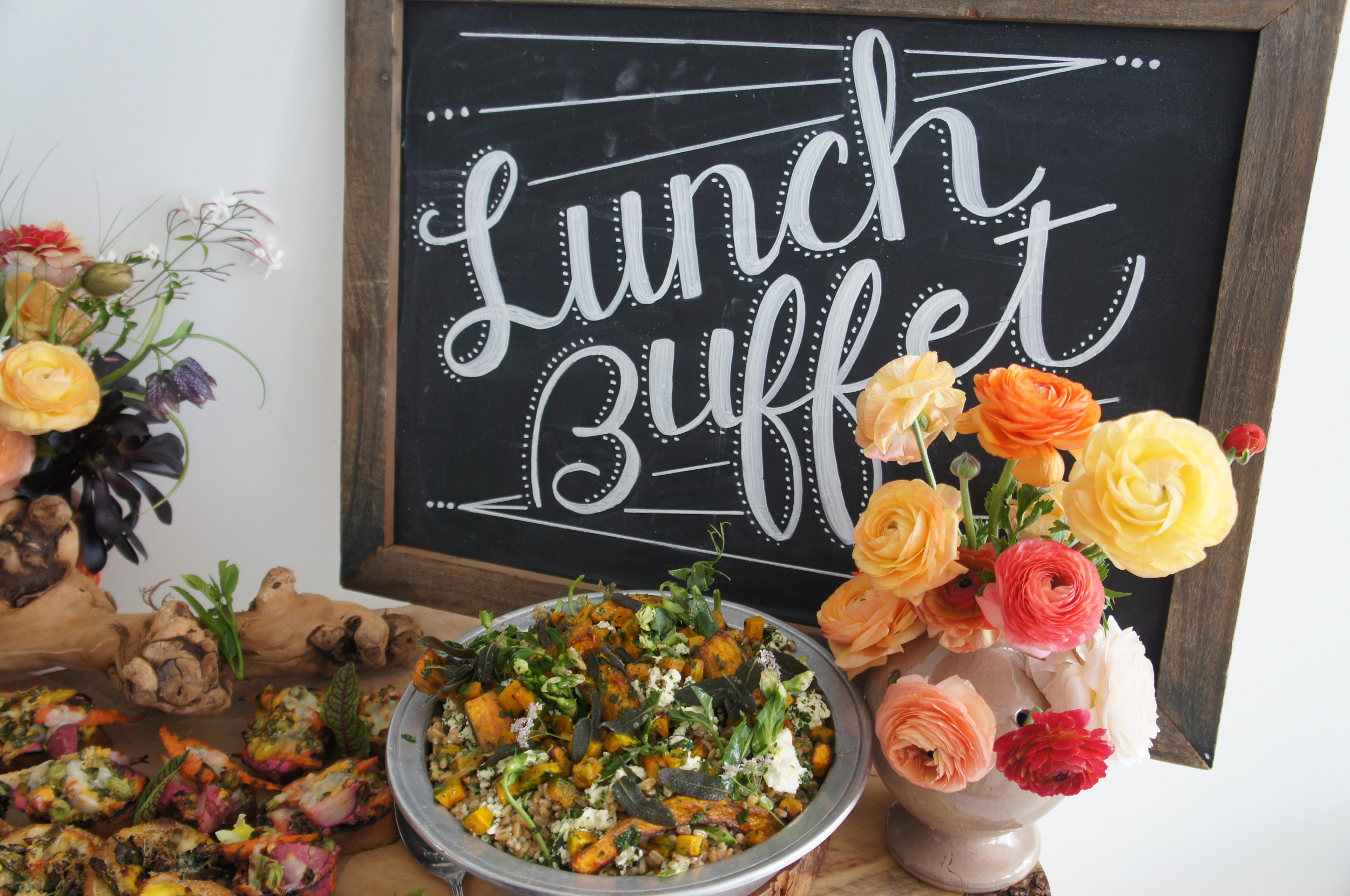 Heirloom LA buffet with hand painted chalkboard and vase of ranunculus
