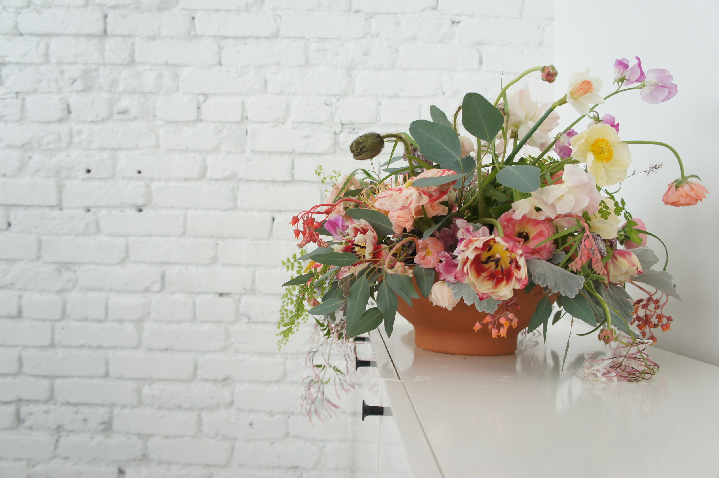 Tablecentre arrangement in low bowl with soft pink flowers
