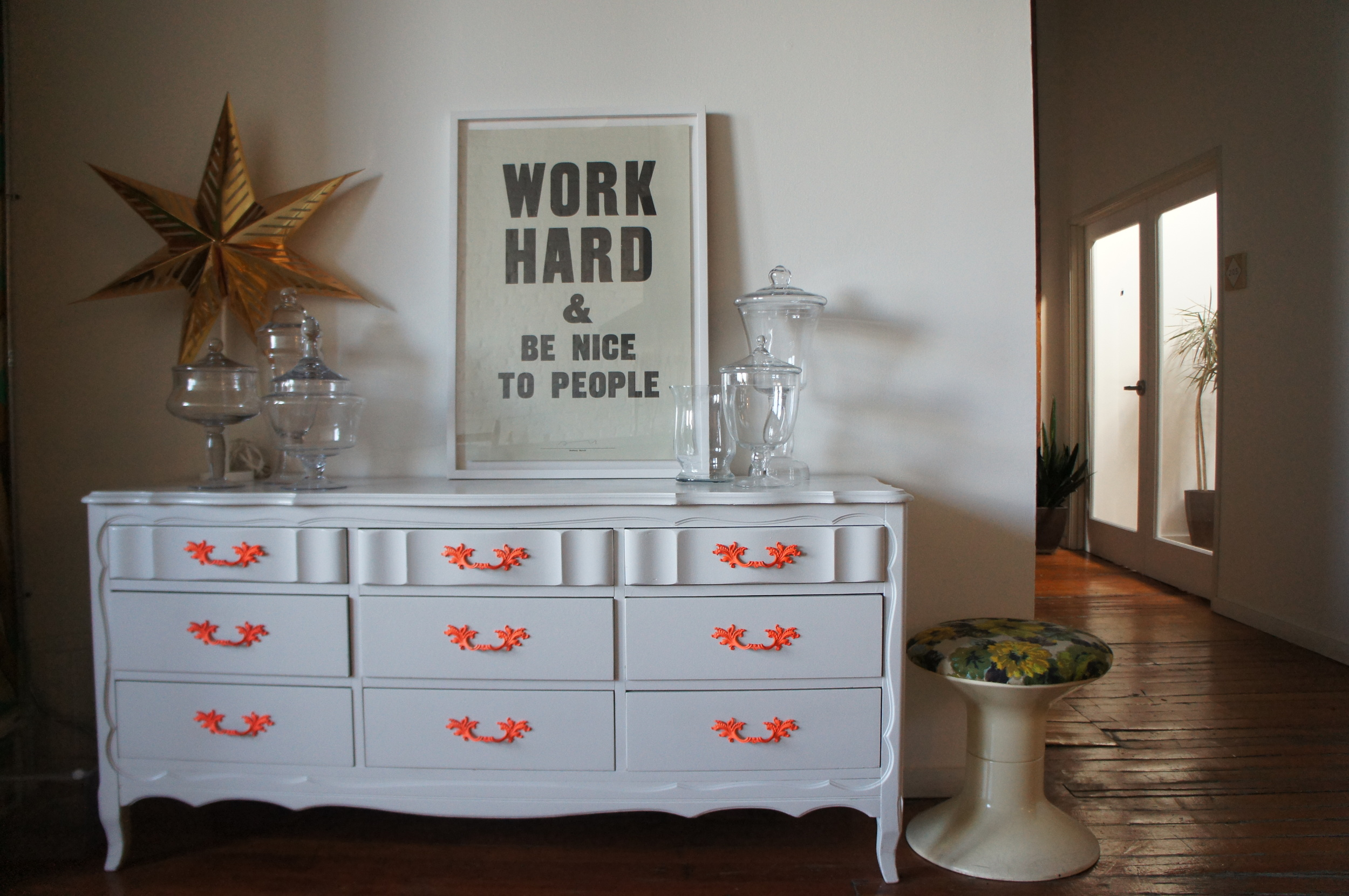 Interior of Unique Space in Los Angeles. White dresser with orange handles, vintage stool, glass vases and poster print