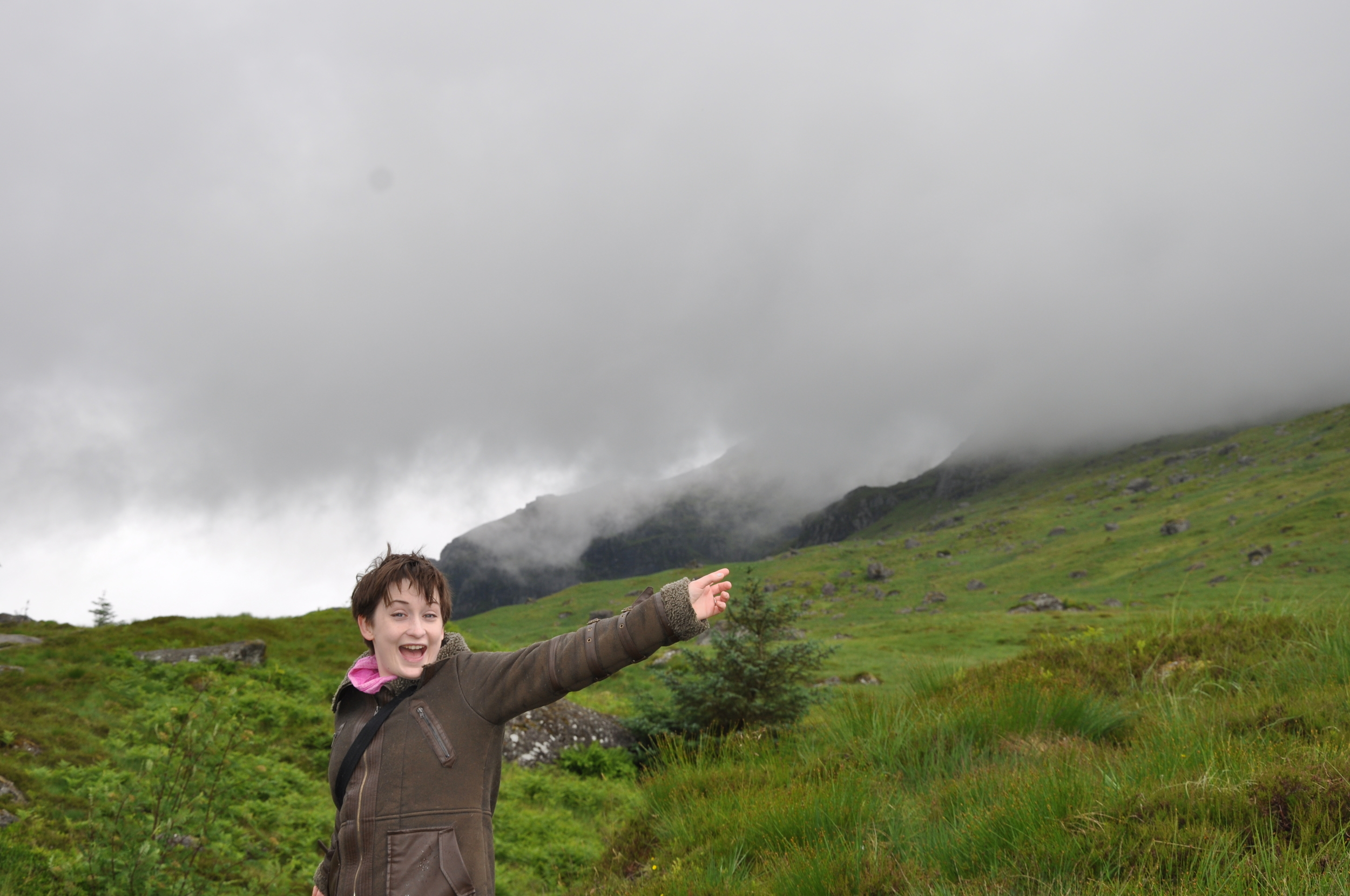 Lady pointing up hill in Scotland