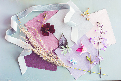 grey velvet ribbon, pink fabric samples and loose flower heads