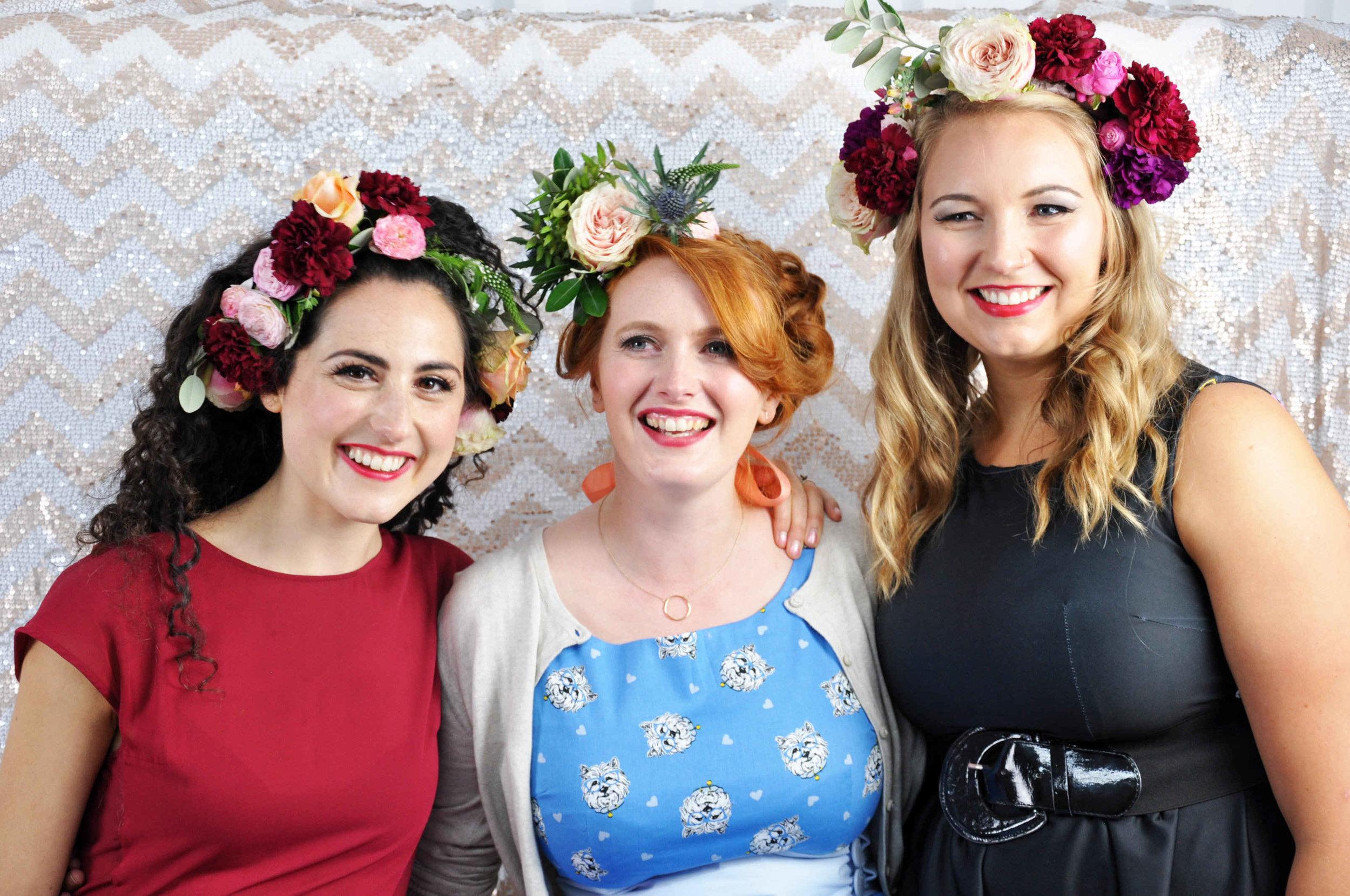 three smiling women wearing flower crown headdresses