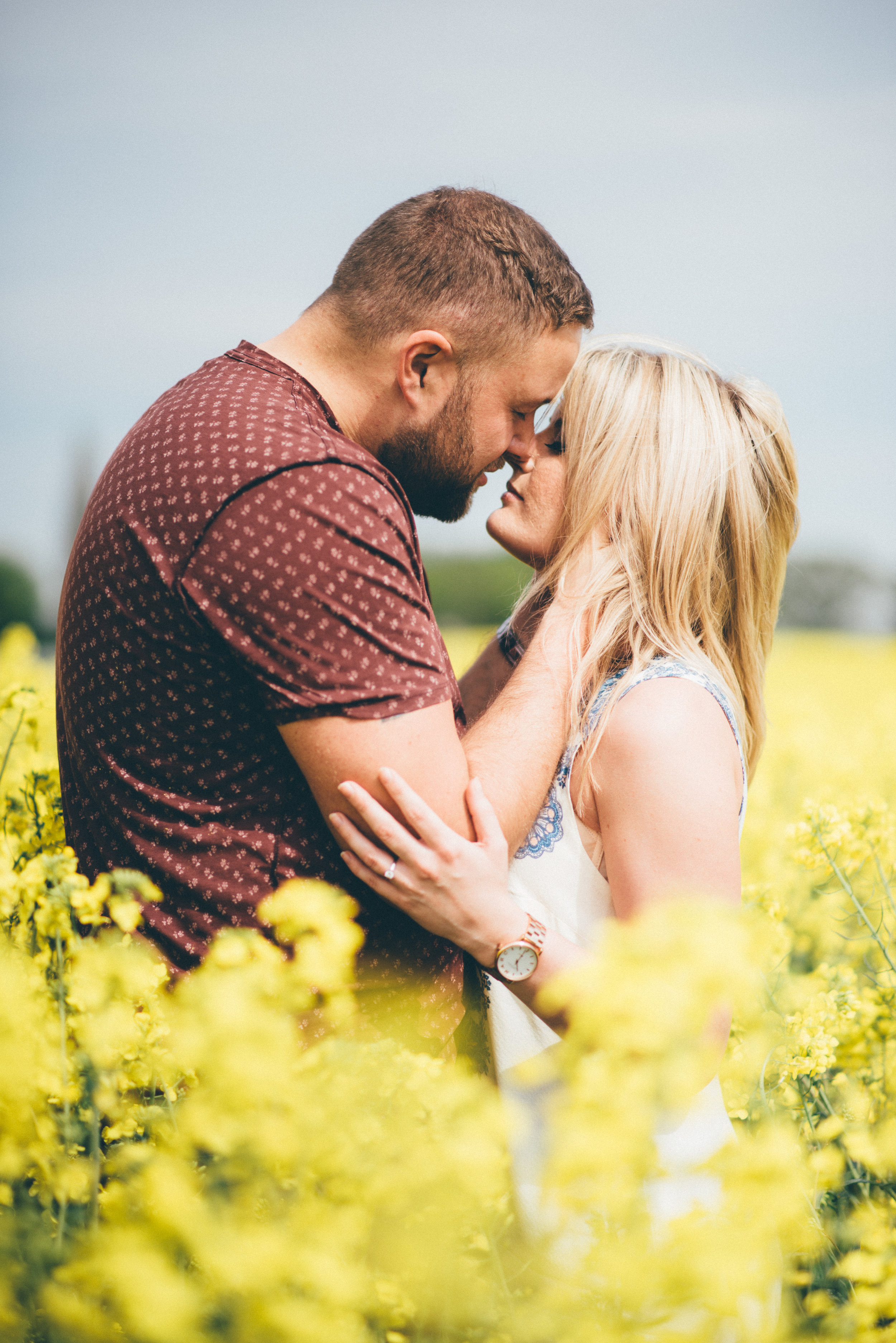 Future husband and wife engage in a incredible embrace in a rape seed field.