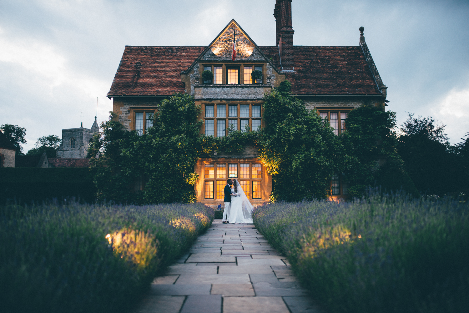 Bride and groom share a kiss at the golden hour in front of their incredible venue, Belmond Le Manoir aux quat'saisons.