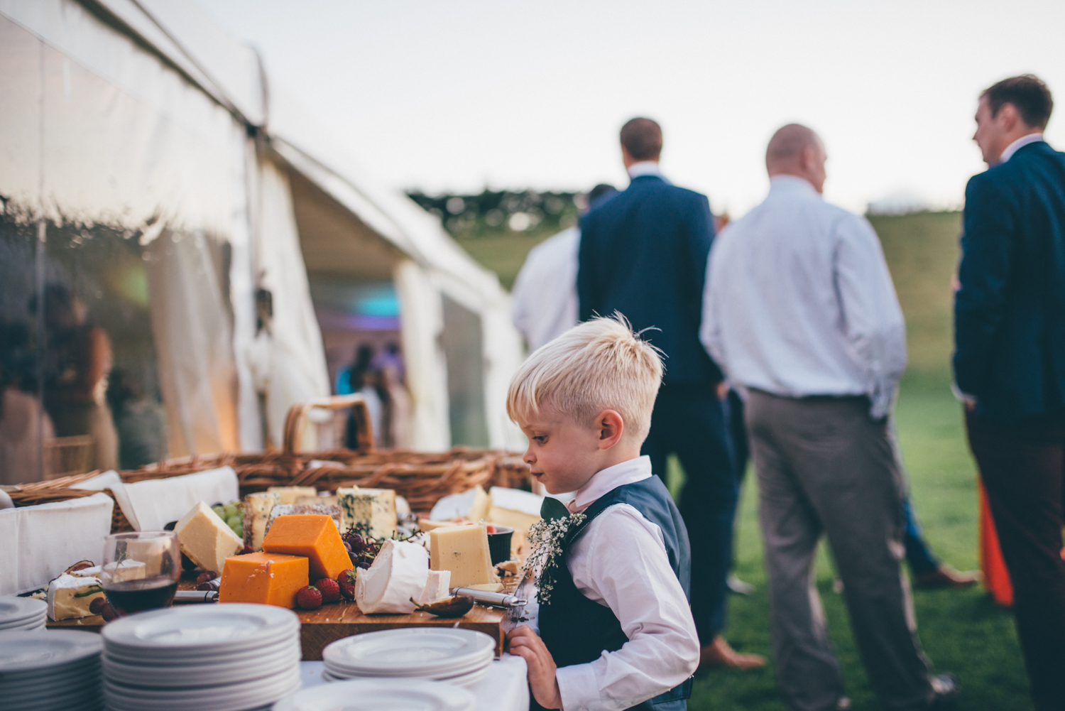 The pageboy stands at the cheese table whilst the adults ejoy the wedding reception at Delamere in Cheshire.