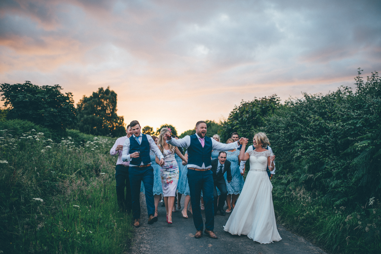 The bride and groom dance through the country lanes in Kingsley, Cheshire with their best friends, all laughing and singing after their wedding breakfast.