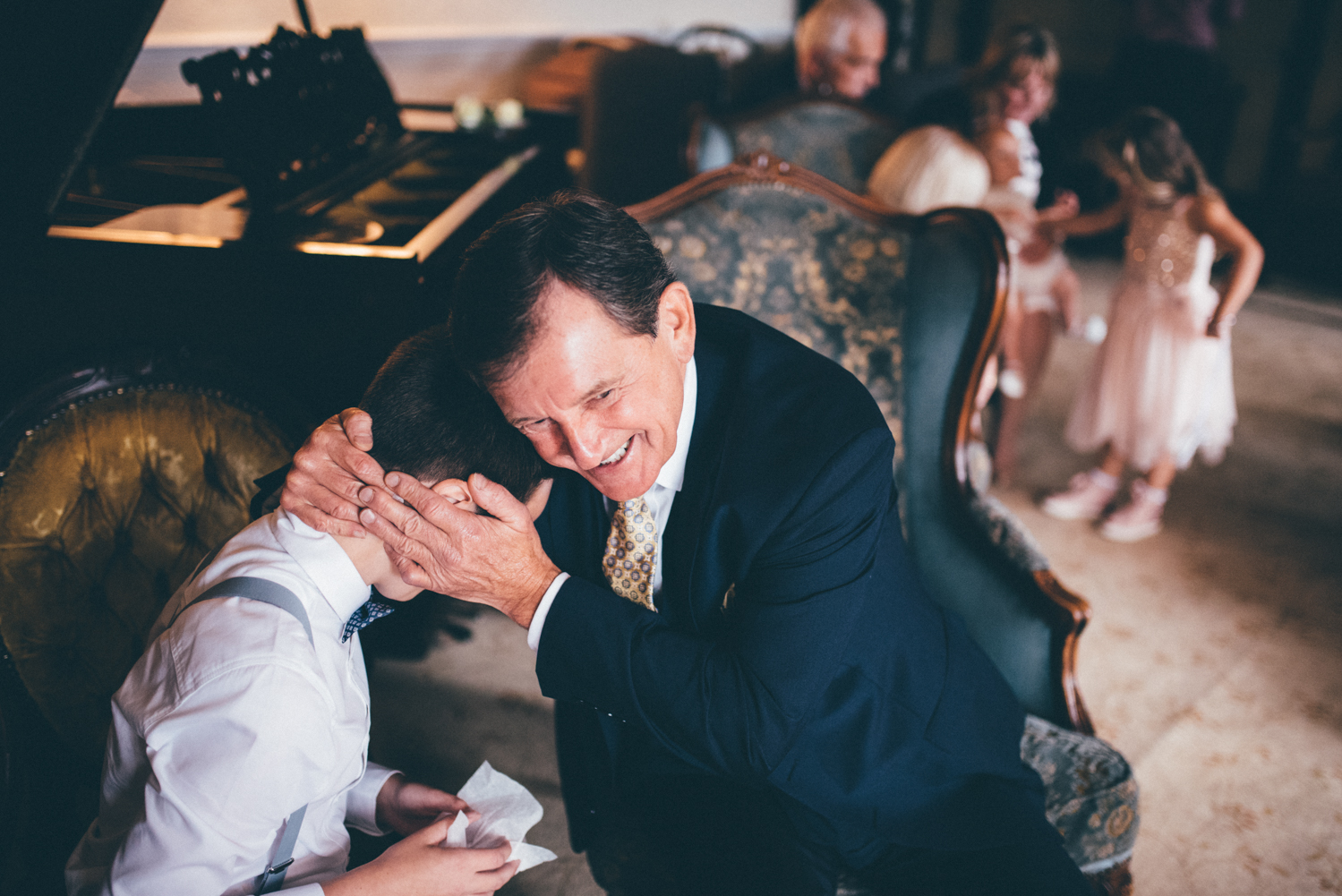 The Bride's son gets hugged by his grandad whilst crying with happiness about the wedding at Langdale Chase Hotel in the Lake District.