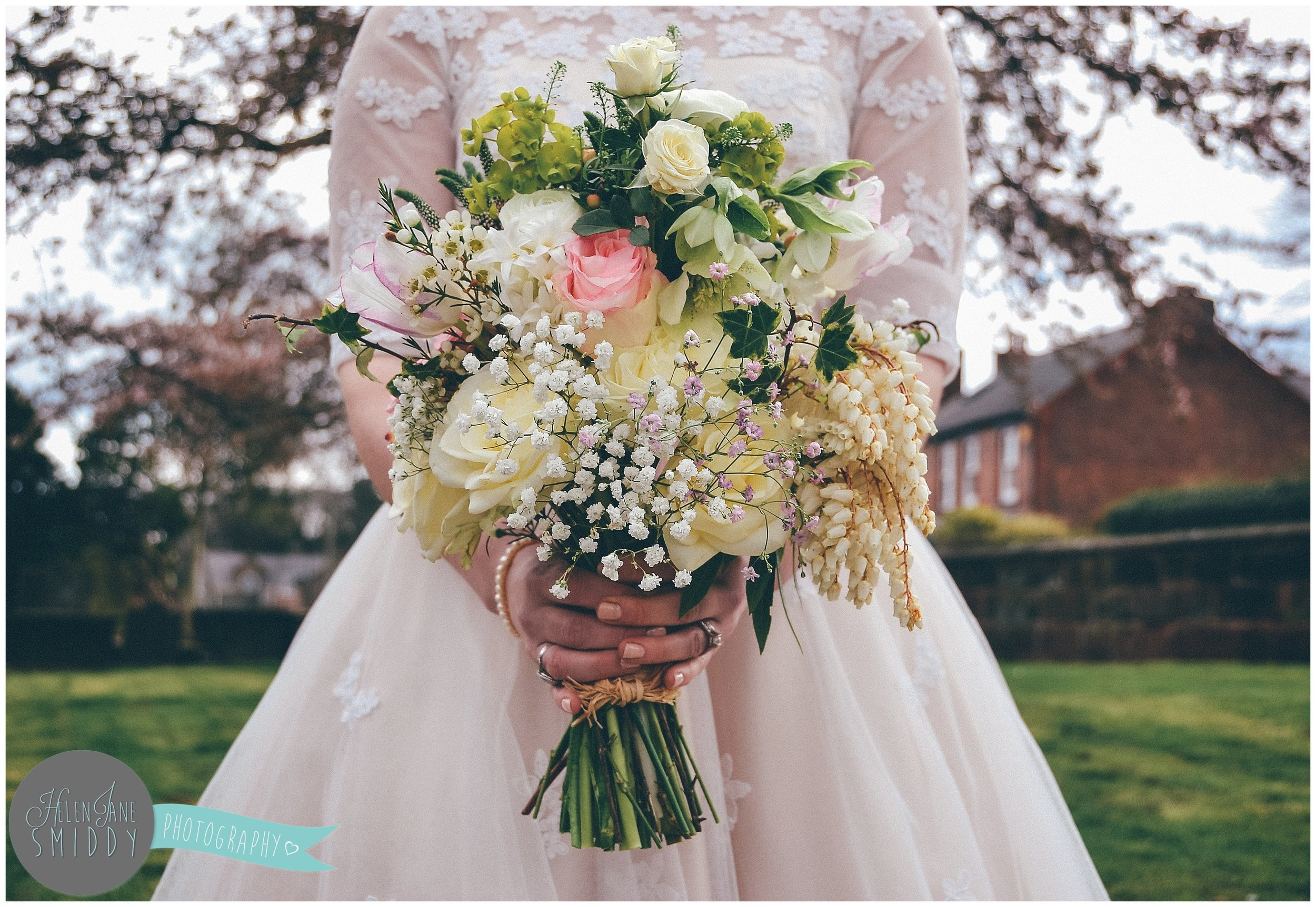 Incredible spring time wedding bouquet, held by the bride.