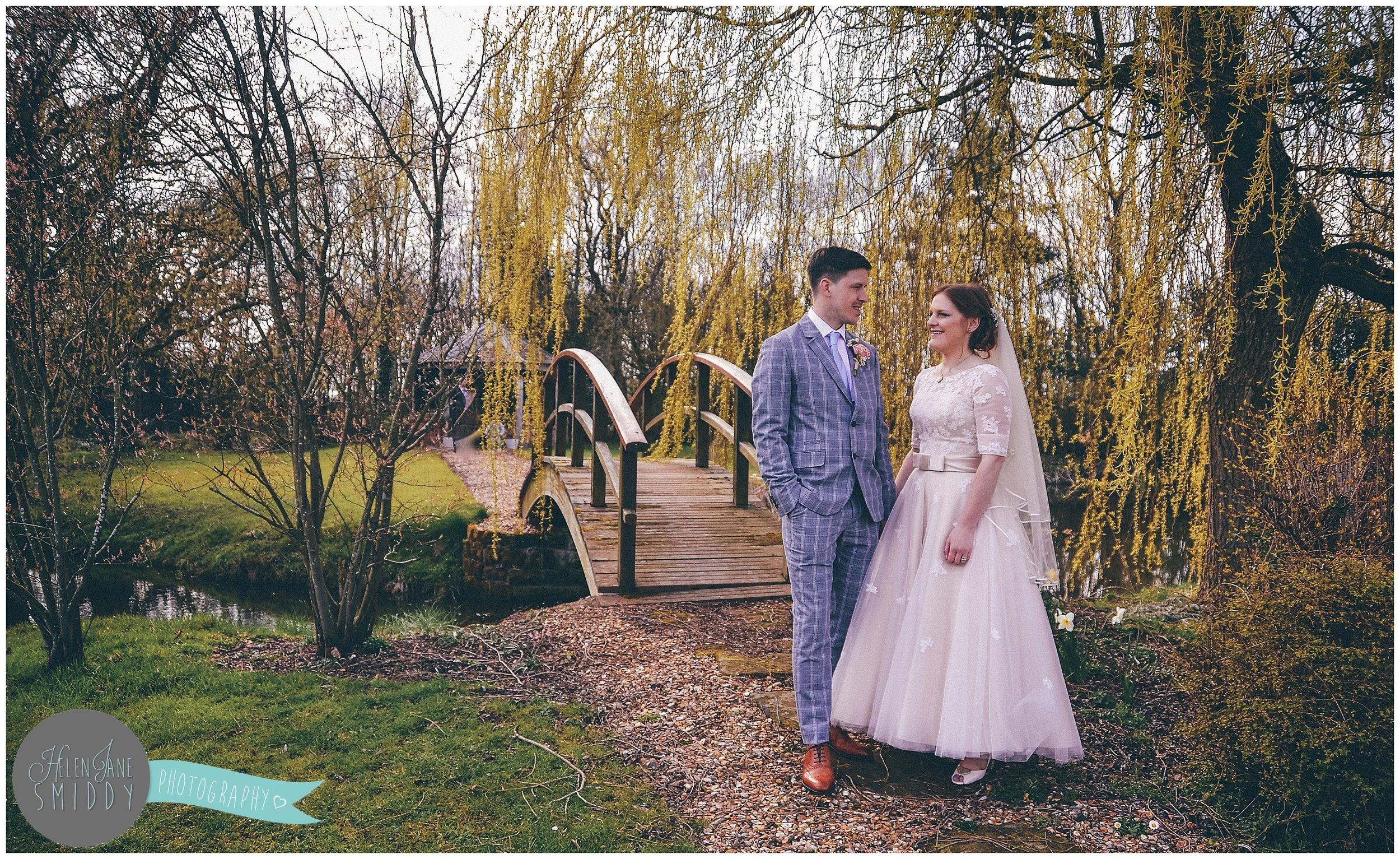 The gorgeous bride and groom stood smiling together in front of the weeping willow.
