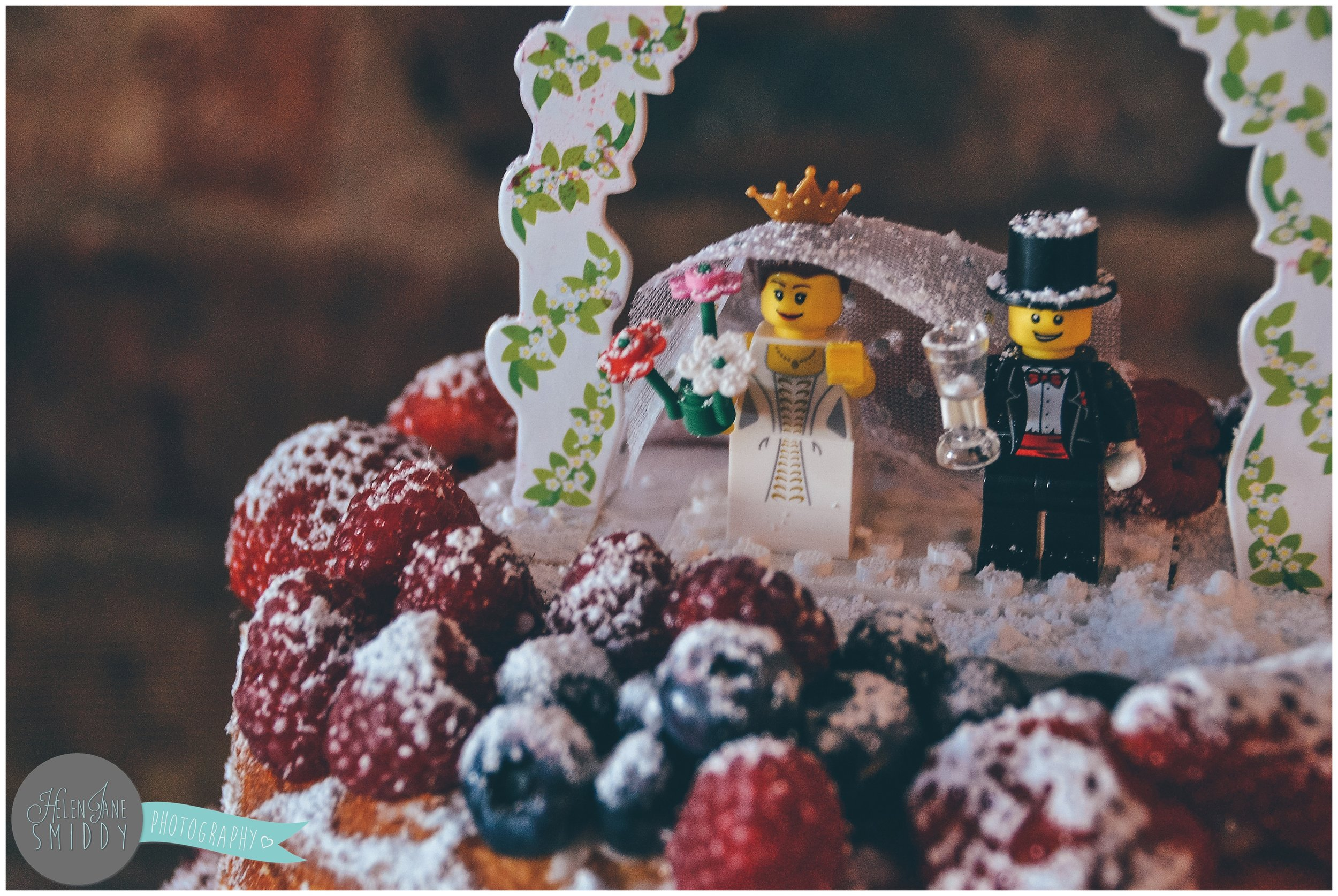 A beautiful homemade wedding cake with lego men toppers.