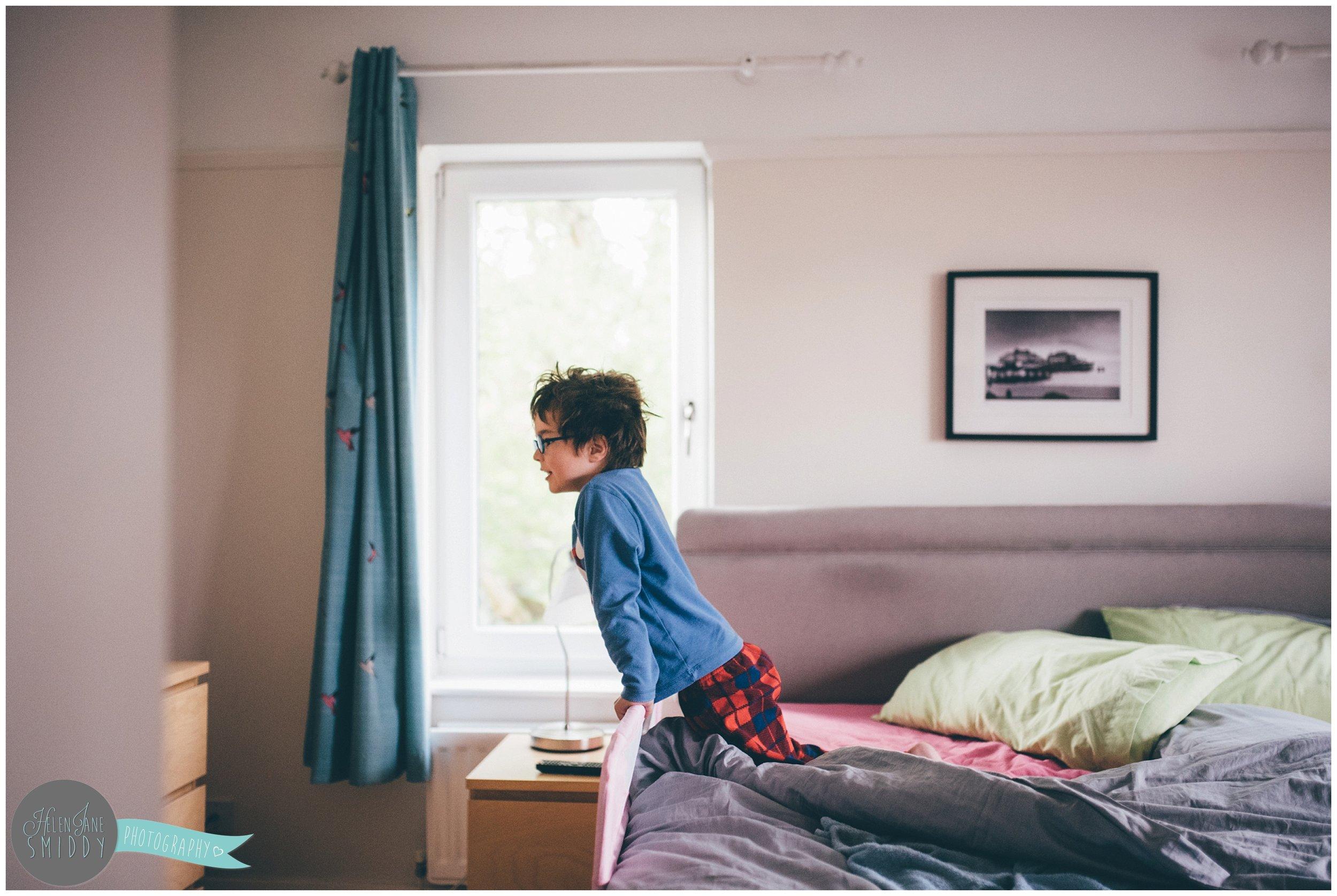 Isaac stares at cartoons on his Mum's bed in his pyjamas.