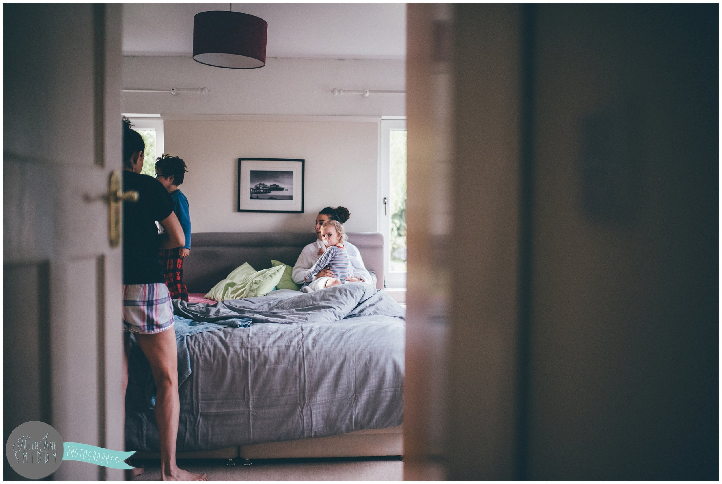 The family sit on the bed, waking up before getting ready for their day.
